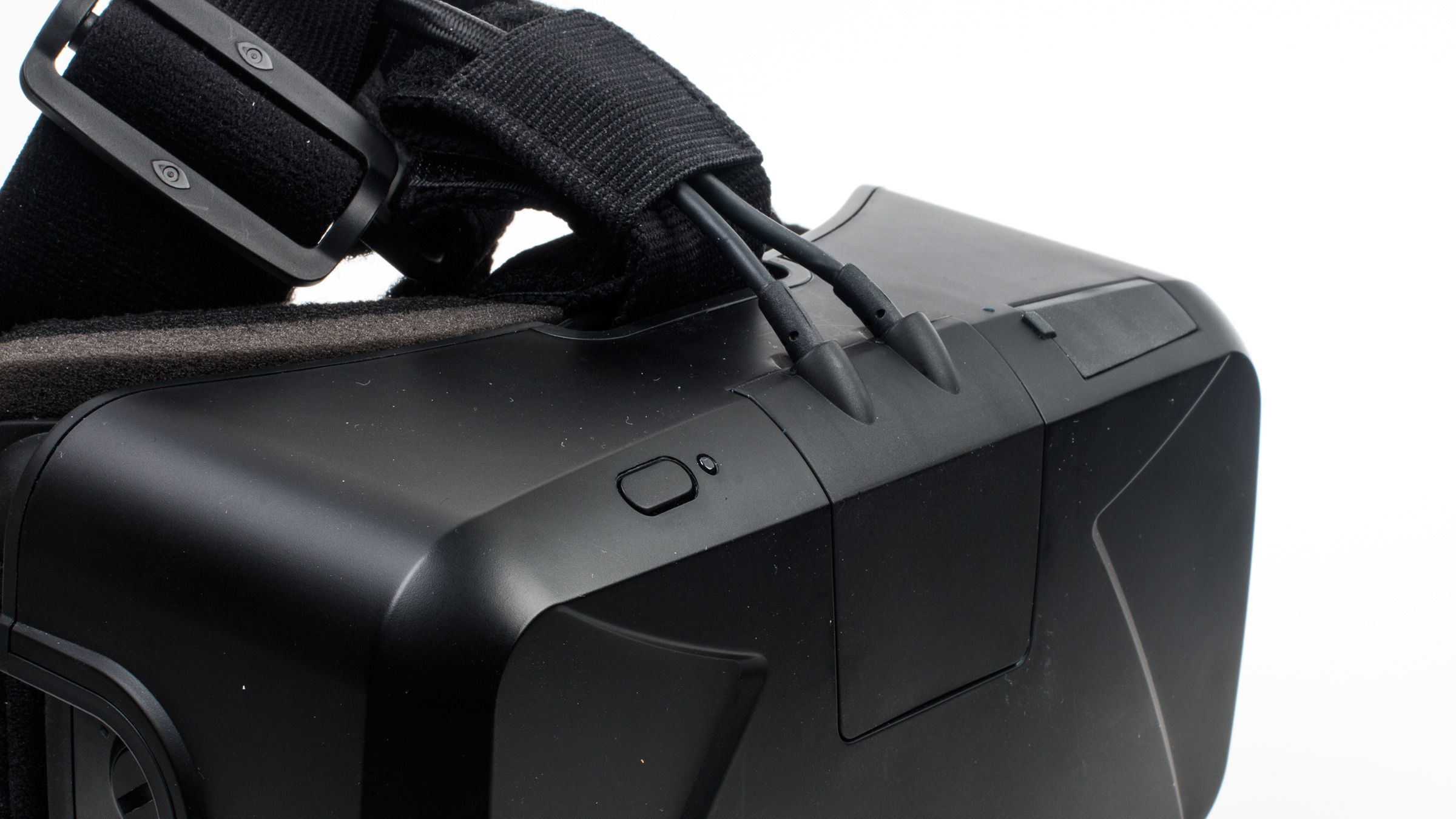 Det nye Rift-hodesettet er betydelig mer kompakt enn det gamle, til tross for at mye av elektronikken er flyttet til innsiden av selve skjermvisiret. På-knappen er ikke lenger festet til en ekstern boks, men befinner seg nå oppe selve Rift-brillen, og her er det også et par kabler som stikker ut.Foto: Varg Aamo, Tek.no