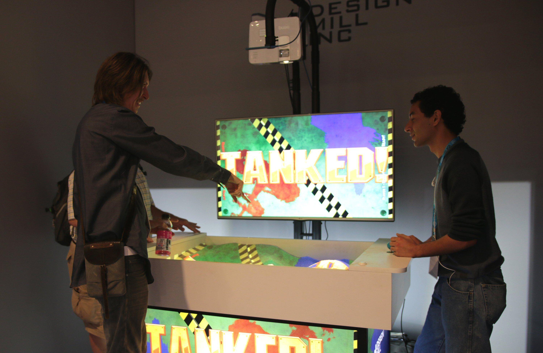 Alex Schuster prøver å forklare spillet. Merk projektoren og RealSense-kameraet over sandkassa. Foto: Vegar Jansen, Tek.no