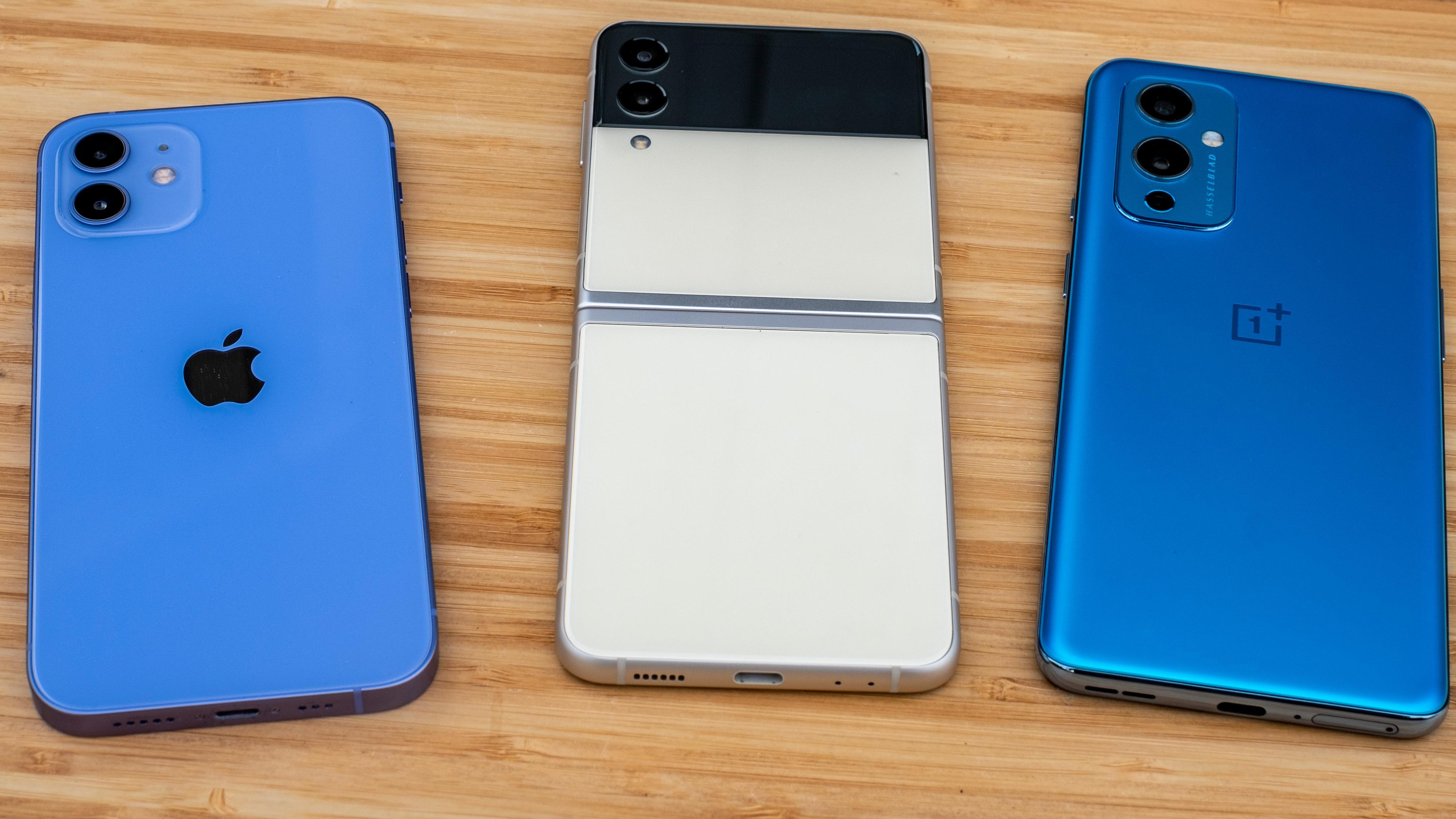 Utbrettet er den på størrelse med en vanlig mobil. Til venstre iPhone 12 i vanlig utgave - til høyre OnePlus 9 - den også i vanlig utgave. I midten Galaxy Z Flip 3.