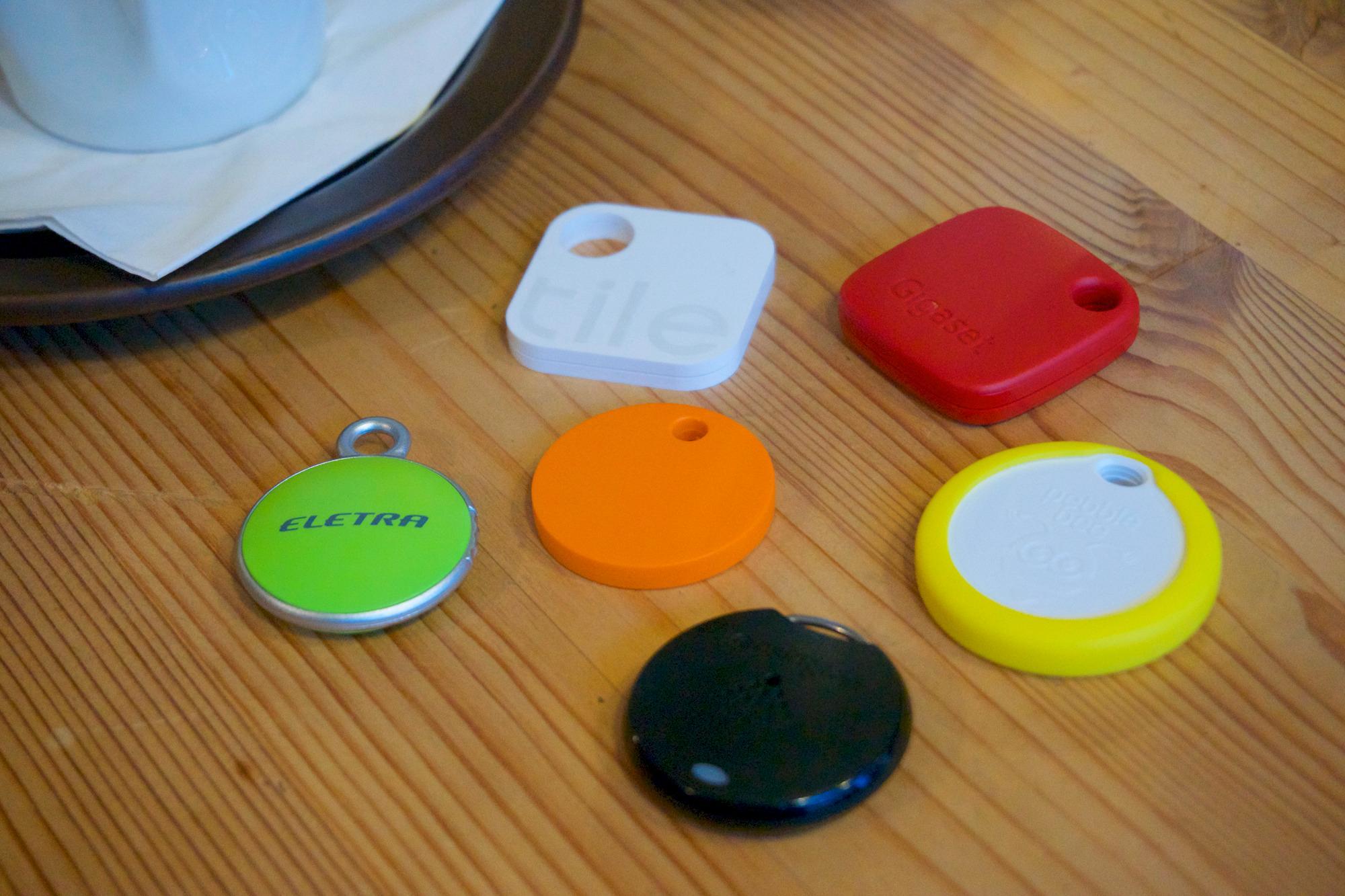 Alle brikkene samlet. Chipolo (oransje) og Eletra Bluetooth Tracker (grønn) er omtrent på størrelse med en 20-kroning, men ingen av brikkene er – som du kan se – spesielt store. Foto: Torstein Norum Bugge, Tek.no