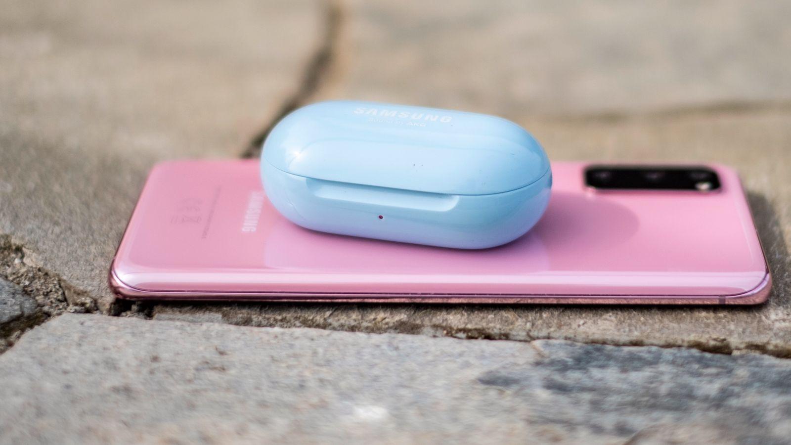Galaxy Buds+ trives best sammen med Galaxy-mobiler. Her lader blå Buds+ på baksiden av en rosa Galaxy S20. Dette er en utmerket kombinasjon både for den beste lyden, flest funksjoner og de mest iøynefallende fargene.
