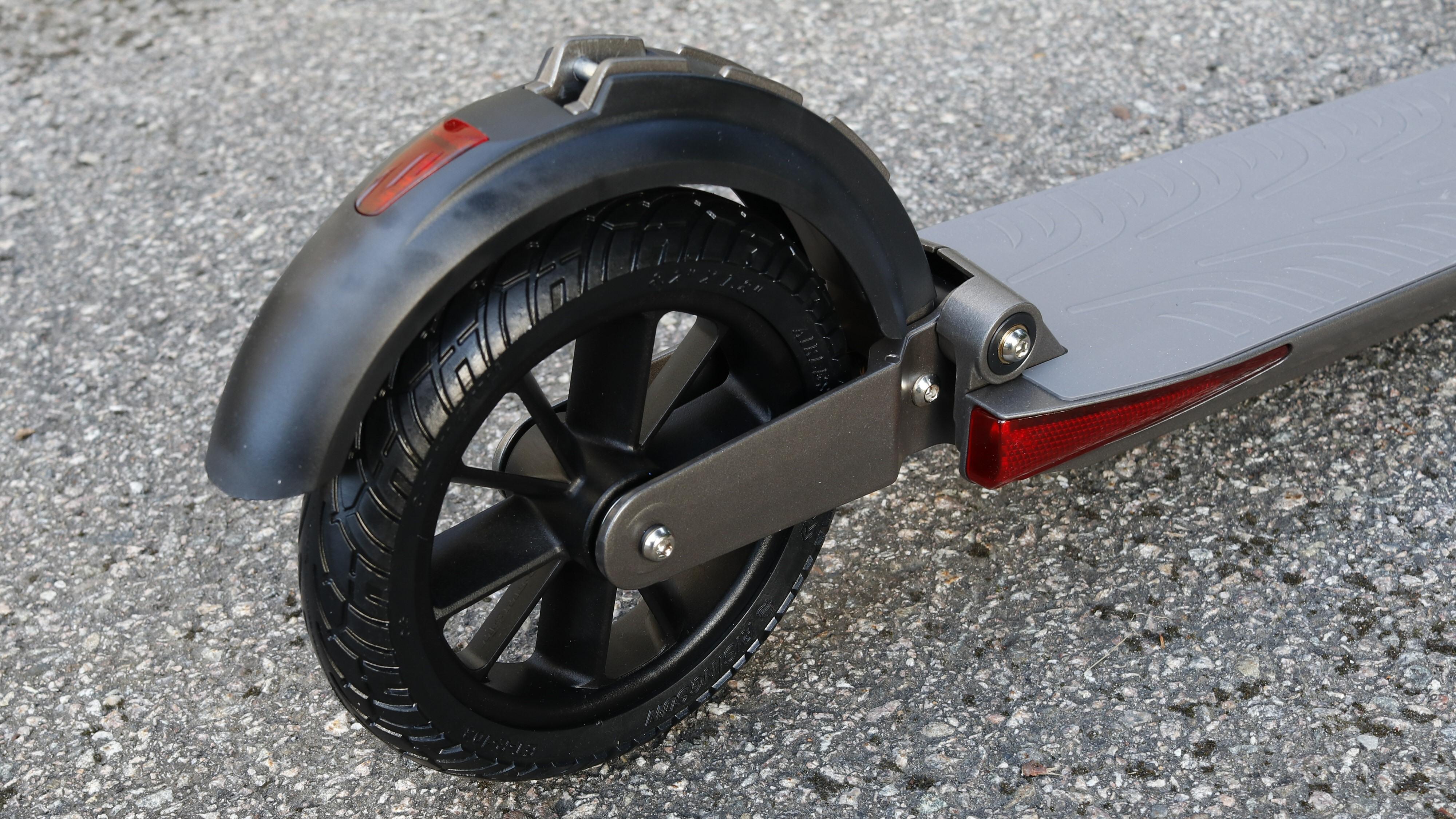 Bakskjermen kan tråkkes ned for å skubbe på hjulet.