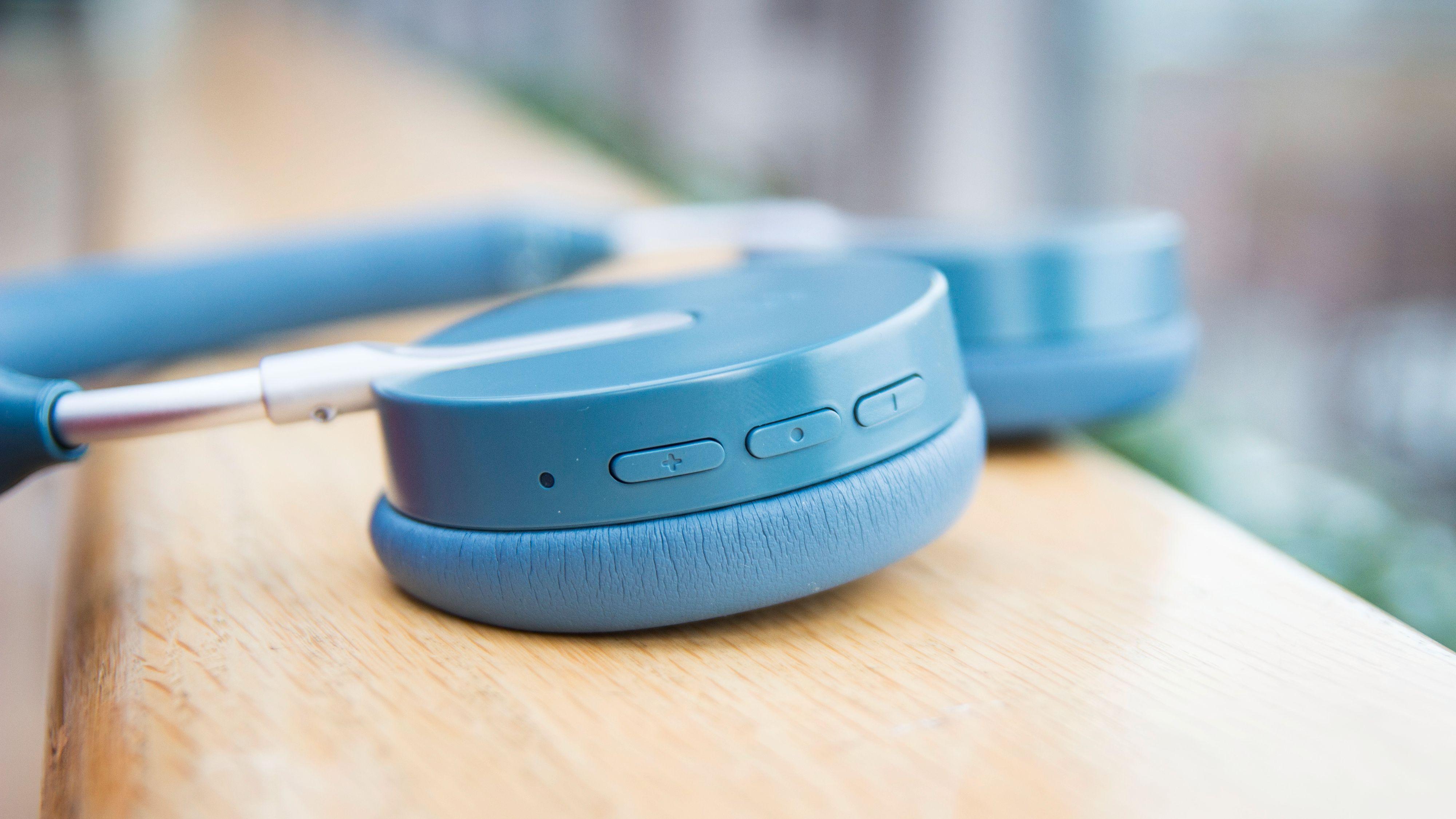 Fysiske kontrollknapper på den høyre øreklokken. Midtknappen fungerer også til å skru hodetelefonene av og på og sette i gang paringsprosessen.