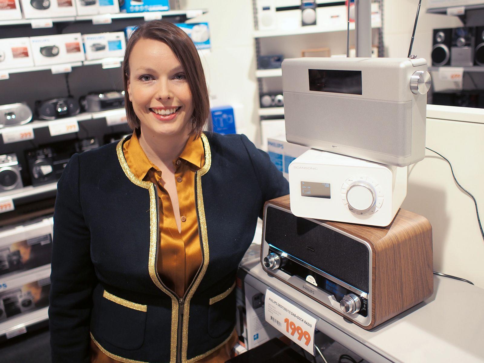 Kommunikasjonssjef Marte Ottemo i Elektronikkbransjen poserer sammen med en annen av salgsvinnerne i 2013, nemlig DAB-radioen.