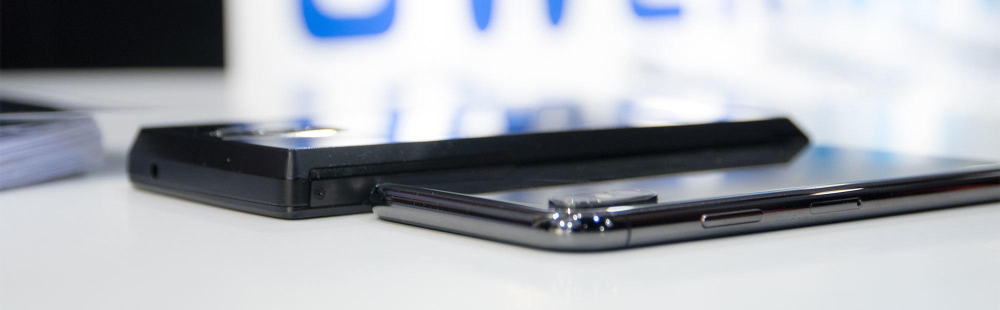 Power Max 16K Pro ved siden av en iPhone X. Den ser ut til å være omtrent dobbelt så tykk og dobbelt så tung.