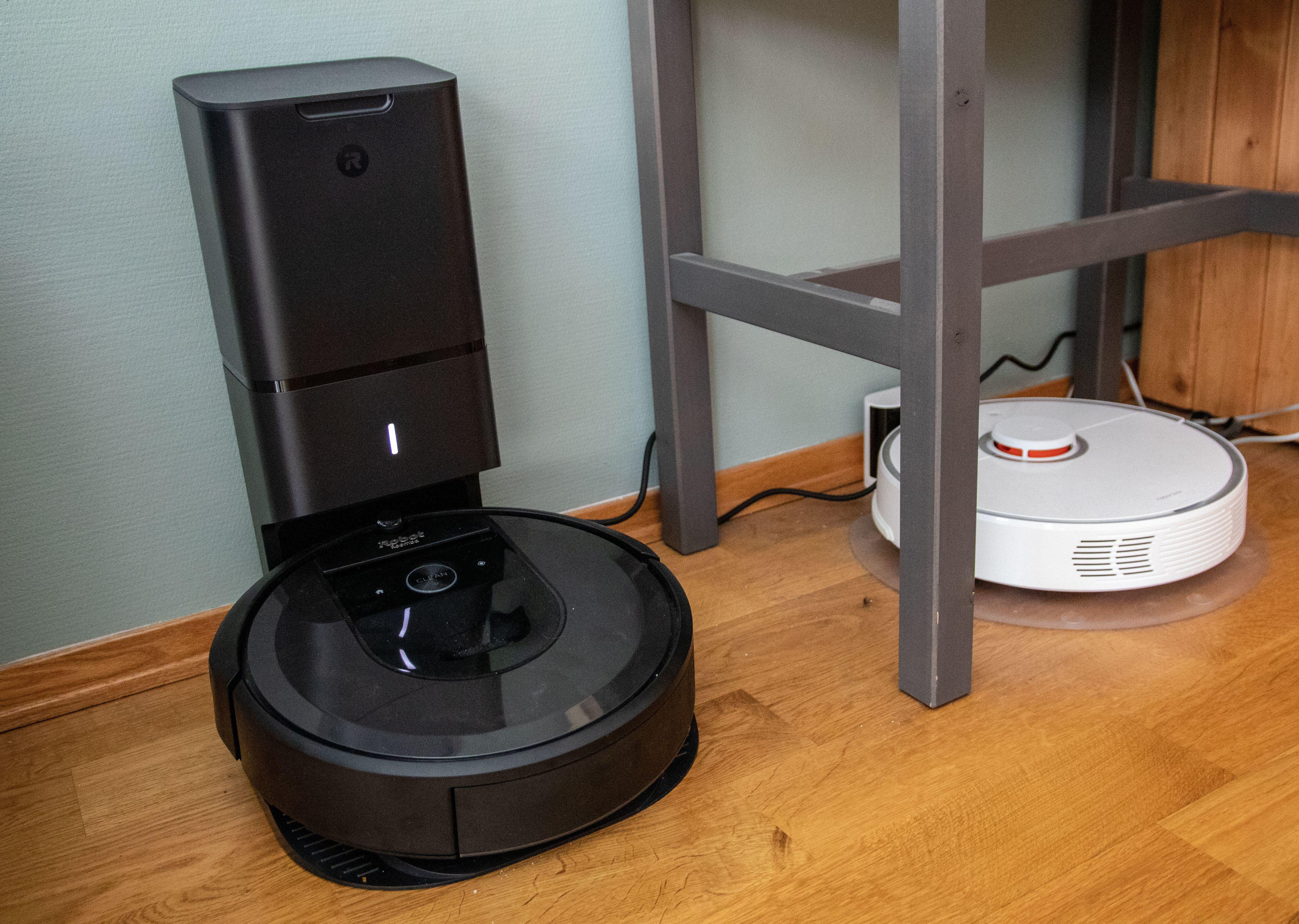 Ladestasjonen til iRobot Roomba i7+ er enorm, fordi den har en innebygd støvsuger til å suge ut alt smuss fra robotstøvsugeren. Her ved siden av den langt mindre ladestasjonen til Xiaomi RoboRock s50.