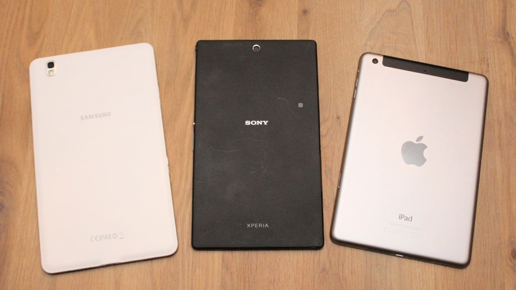 Baksiden på Xperia Z3 Tablet Compact er dørgende kjedelig, uten at det egentlig gjør noe. Til venstre Samsung Galaxy Tab Pro, som har en bakside i imitert skinn. Til høyre iPad Mini 3, som har en bakside i metall. Foto: Espen Irwing Swang, Tek.no