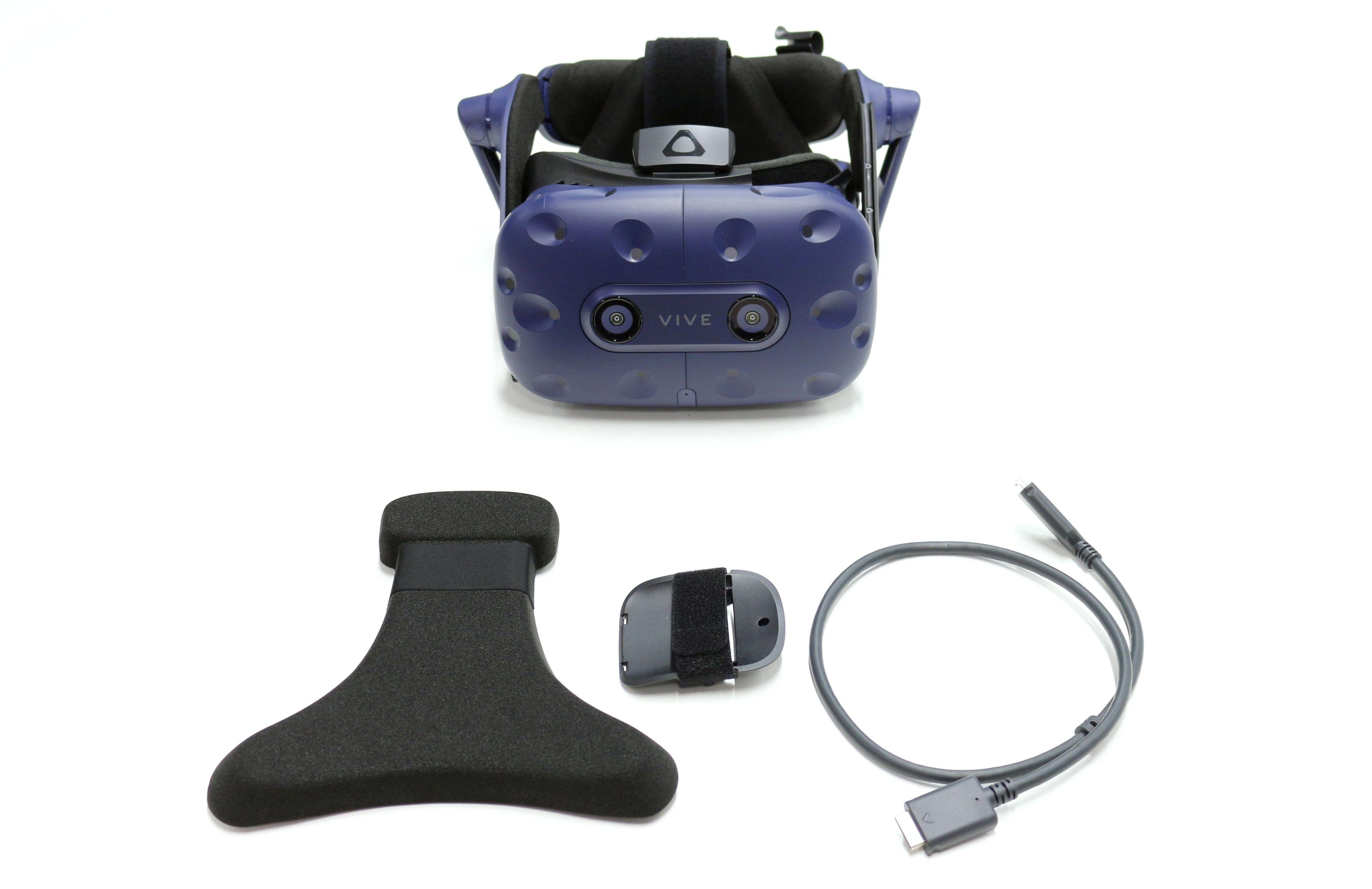 Vive Pro i bakgrunnen og de tre komponentene som utgjør «HTC Vive Pro Wireless Adapter Attachment Kit» i forgrunnen.