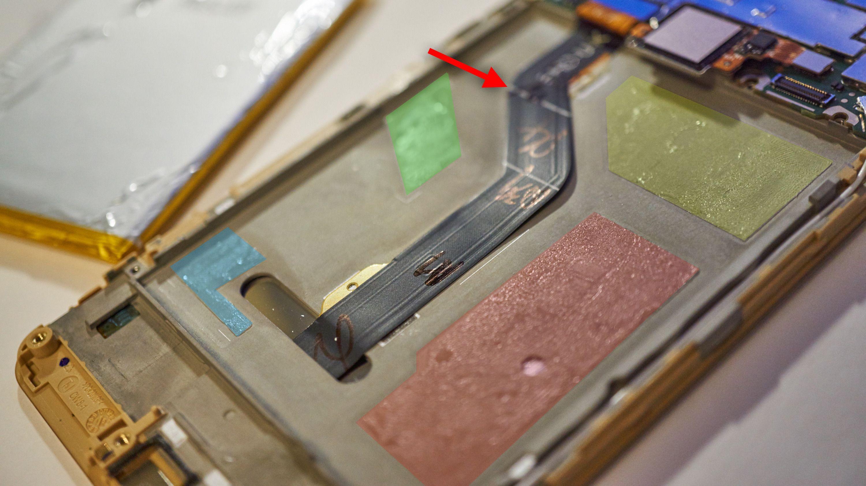 Her har vi markert de forskjellige områdene med lim i farger. Det grønne området er limet vi dro ut med pull tab-en, mens pilen markerer kabelen vi mistenker den skal beskytte.