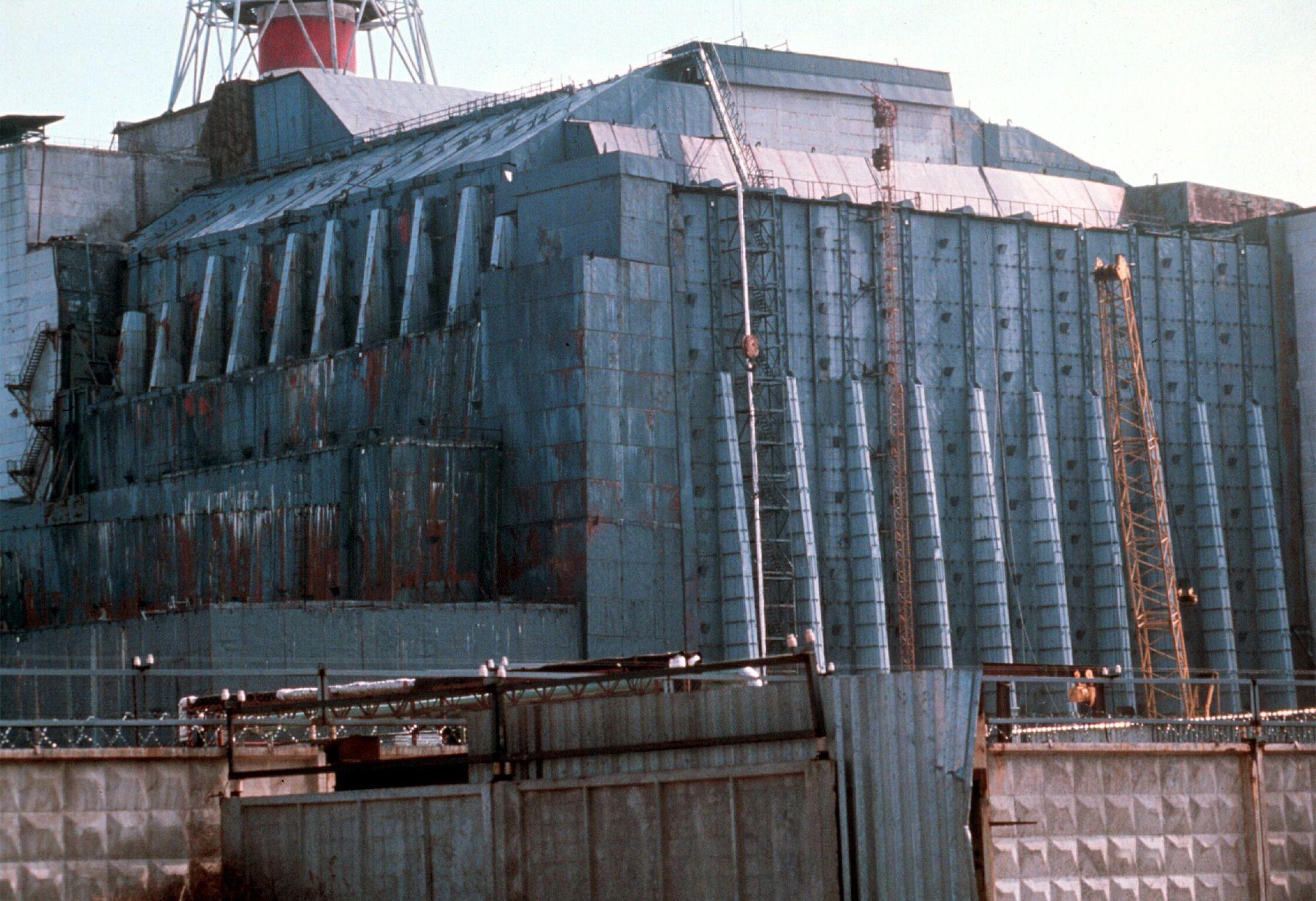 Etter en katastrofal ulykke i Tsjernobyl-kraftverkets reaktor nummer fire i 1986 ble denne enorme betongsarkofagen konstruert i full fart rundt reaktoren, for å hindre radioaktivt materiale i å slippe ut. Den er nå i ferd med å erstattes av en enorm stålsarkofag, som skal stå der i minst 100 år fremover.Foto: NTB scanpix