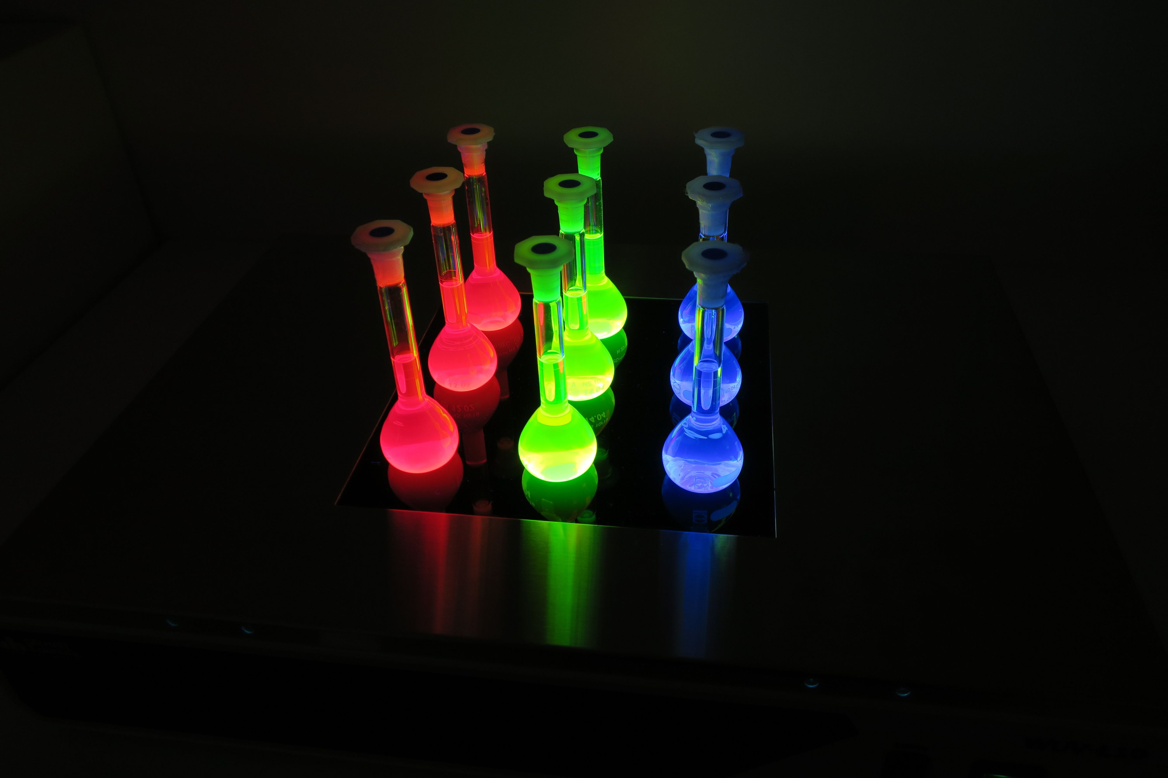 Her ser du flasker fylt med forskjellige størrelser kvanteprikker. Tilføy litt lys og fargene våkner til liv.