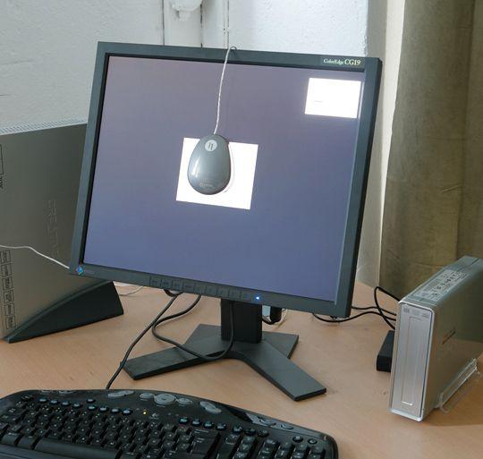 Eksempel på oppsett for kalibrering av skjerm. Kolorimeteret, i dette tilfellet Eye-One Display 2, ligger an mot skjermen, slik at det kan