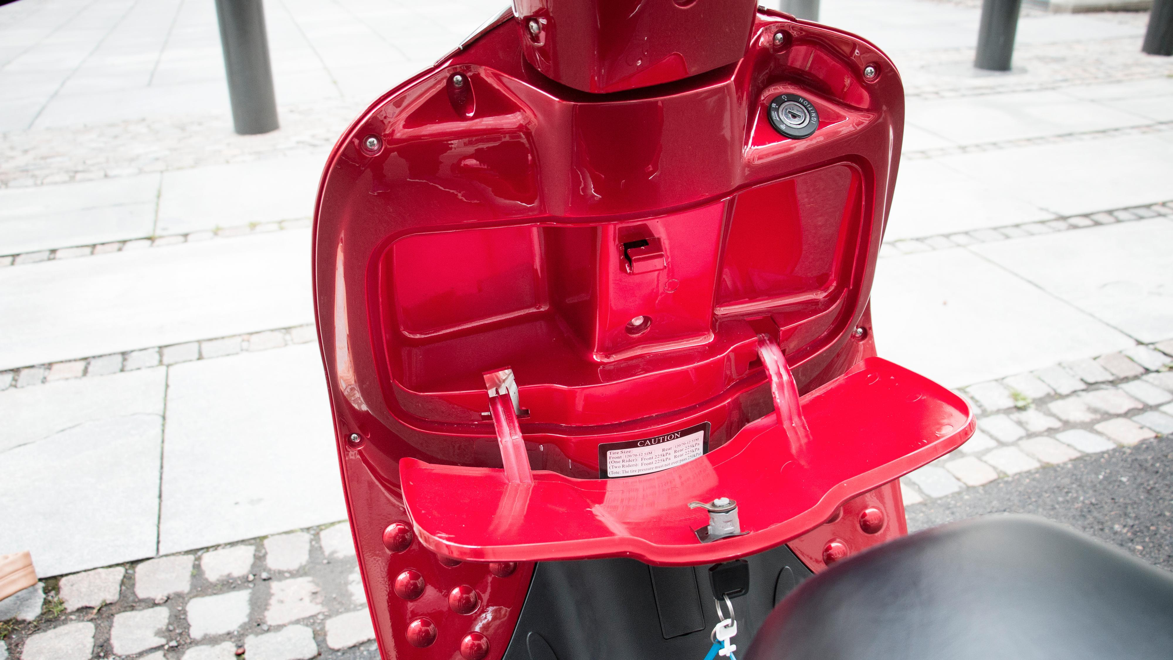 Foran på scooteren finnes det et lite oppbevaringsrom. Både luka og plasthengslene virker imidlertid svært lite solide, så her gjetter vi kanskje at det kan bli trøbbel med holdbarheten etter hvert.