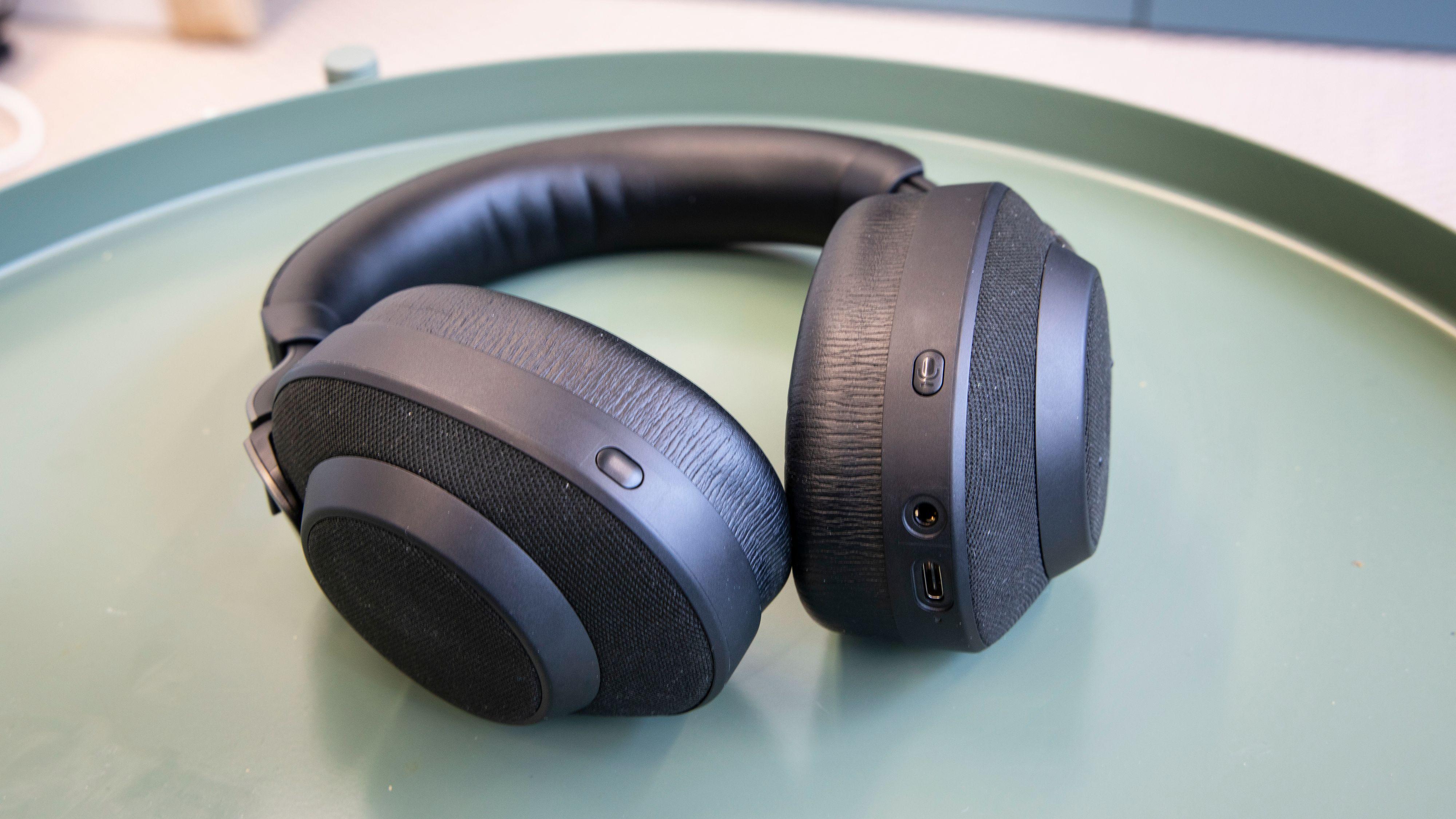 Knappen på høyre øreklokke brukes til å aktivere taleassistenten, mens knappen på den venstre bytter mellom støydempingsmodusene.