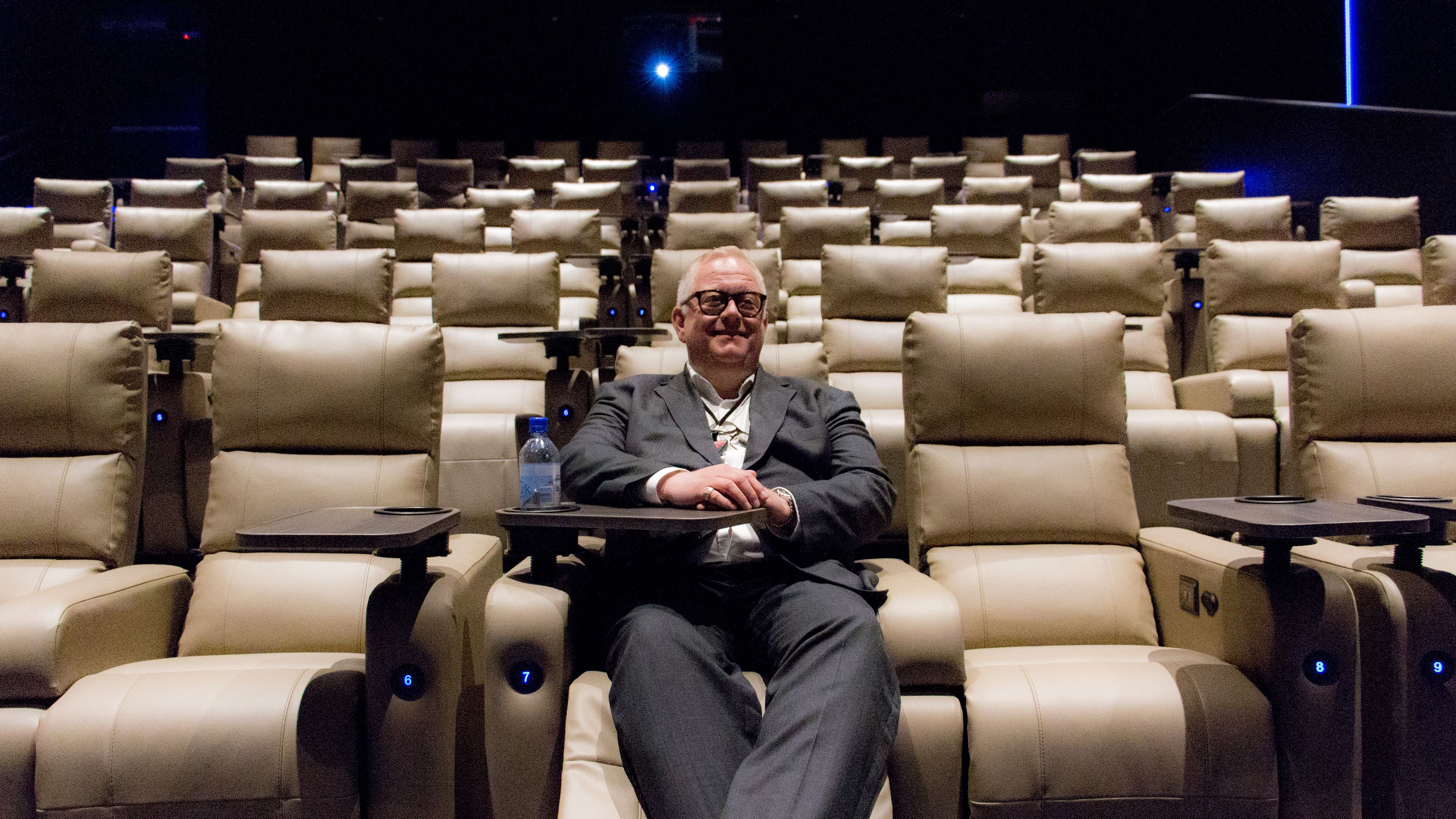 Kinosjef Halstvedt demonstrerer lenestolene i Luxe-salen, som har høy komfort, lademuligheter for mobil og til og med varme i setene.
