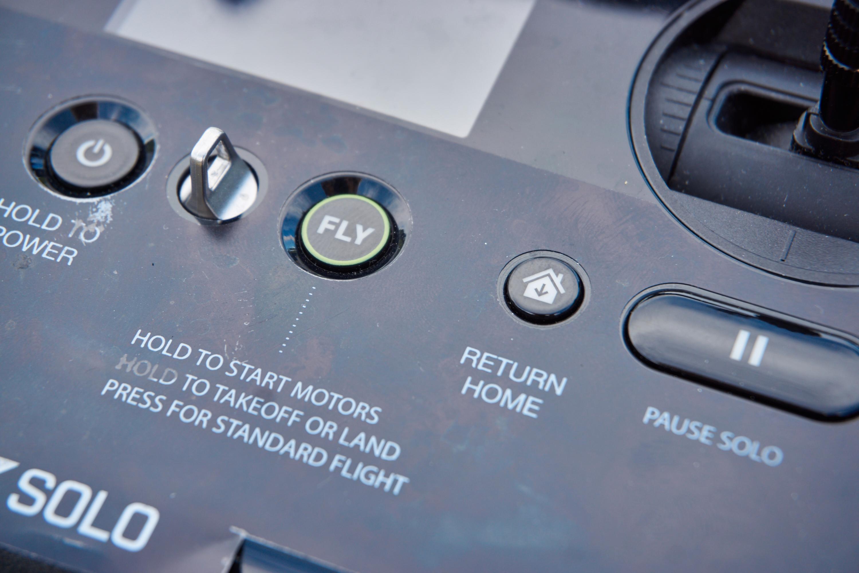 Ved hjelp av disse knappene kan du både ta av og redde dronen om du skulle få panikk. Den sølvfargede hanken i midten er til å feste halskjede i, for å sikre kontrolleren.