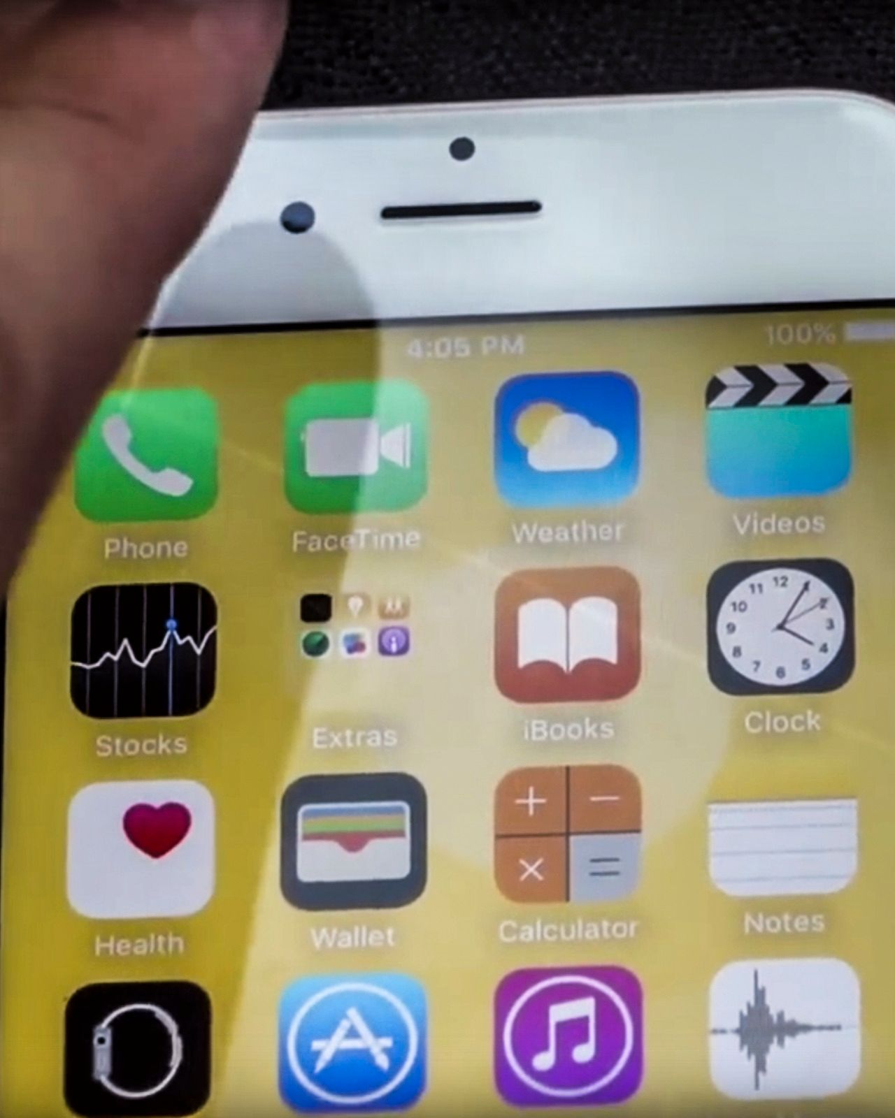 «Skaden» på skjermen kan så vidt skimtes som en lysere stripe som går diagonalt fra toppen av telefon-symbolet og ned gjennom FaceTime-, iBooks- og Clock-appene. Vi har forsterket kontrasten for å tydeliggjøre stripen. Foto: Zach Straley/YouTube | Redigert: Tek.no