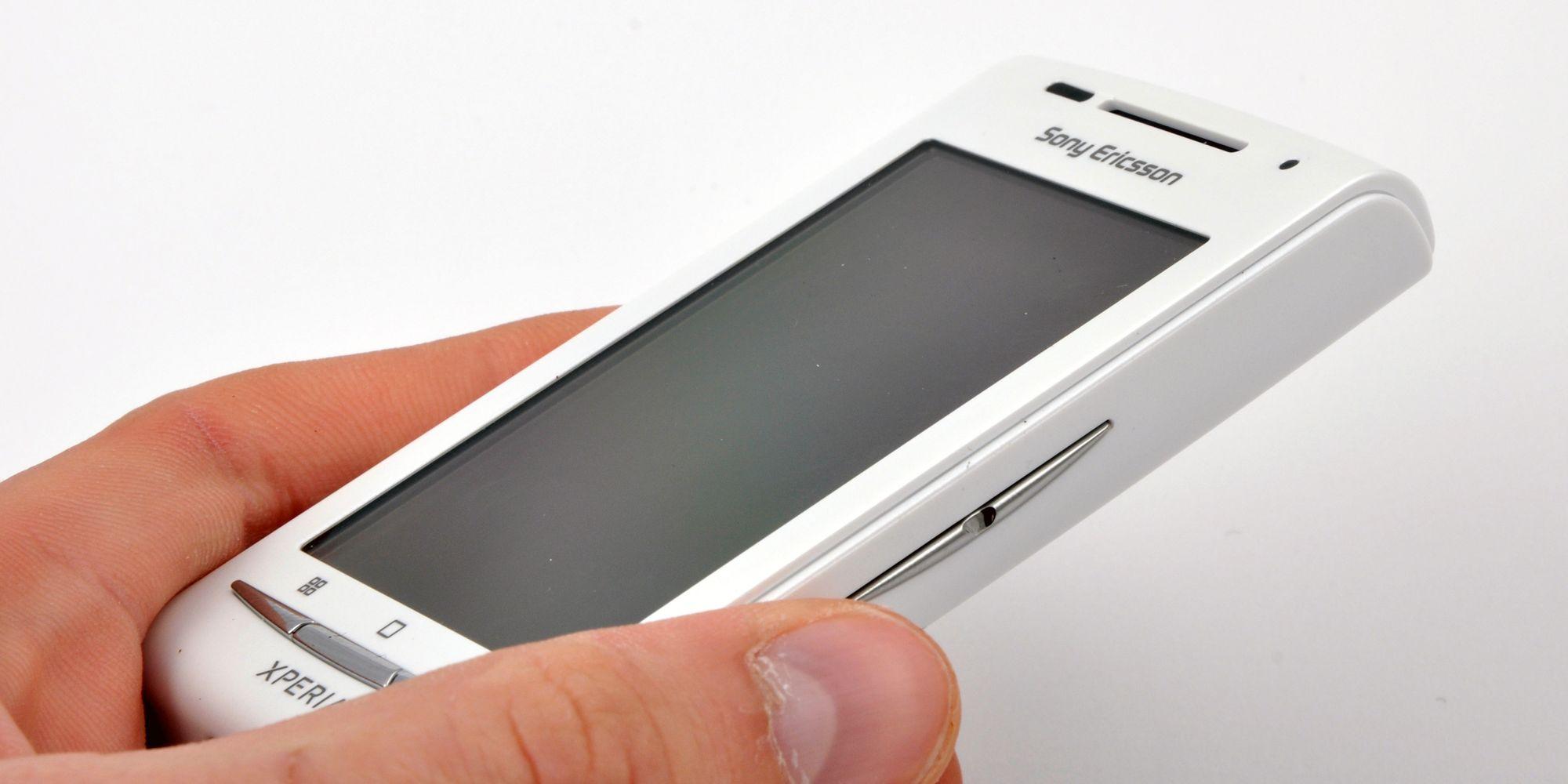 Mobil Sony Ericsson Xperia med lader, ørepropper og