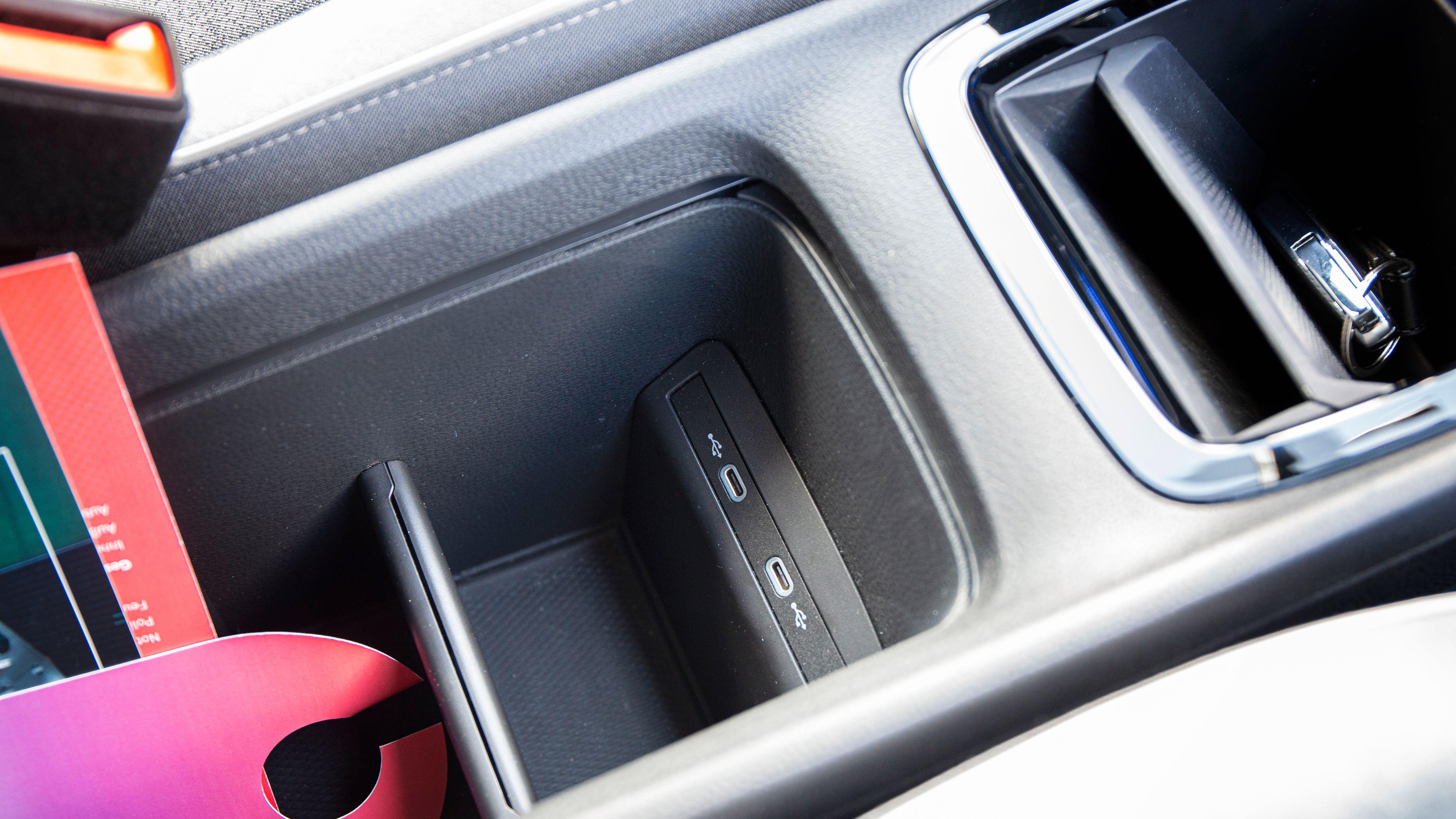To USB-C-porter mellom setene. Trådløs lading av mobil er tilvalg, og ligger i den lille glippa ved siden av nøklene på bildet.