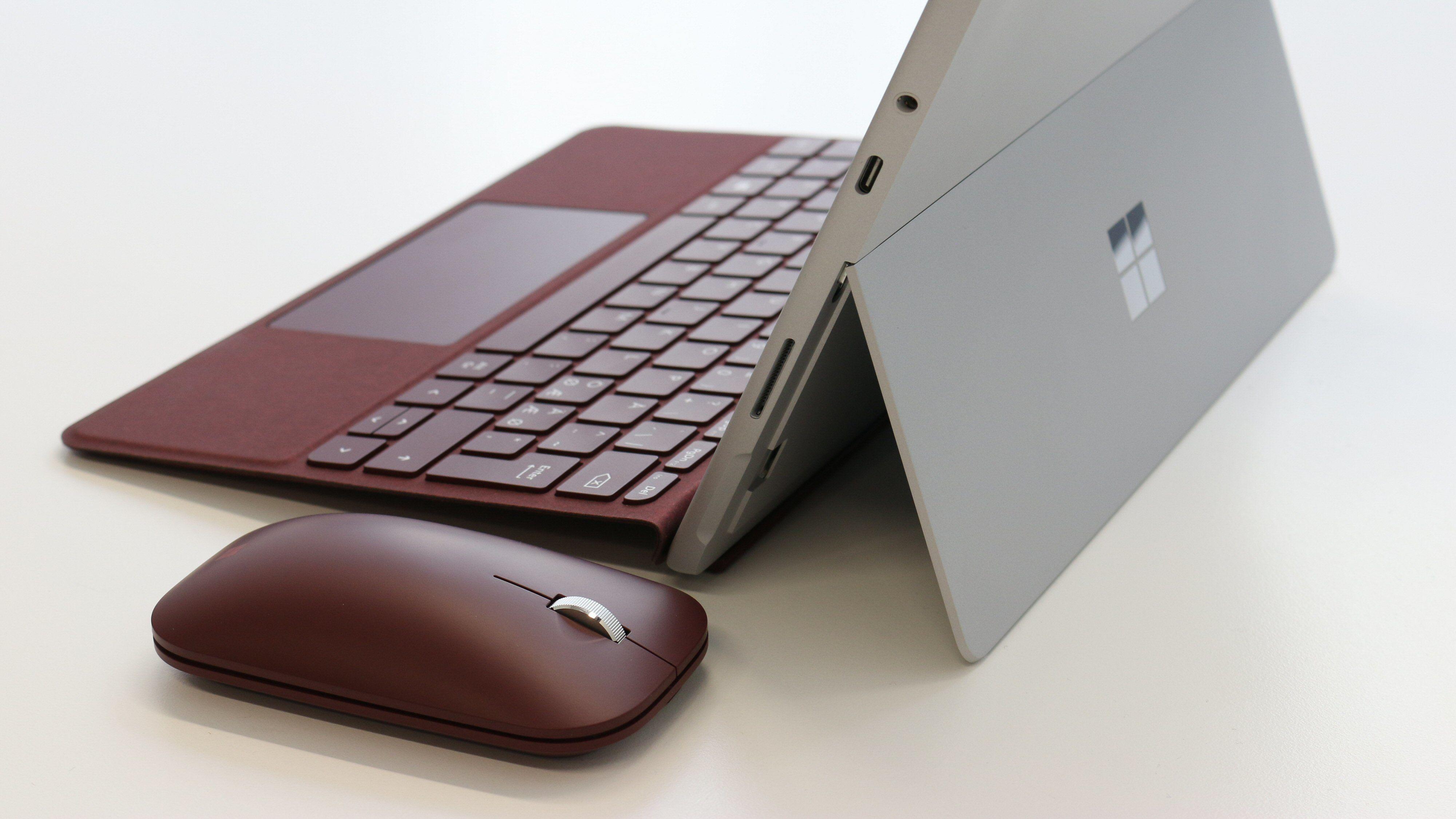 Alle porter er nå samlet på høyre side: Surface, USB Type-C, minijack for lyd og plass til microSD-minnekort bak støttebeinet. Her ser du også Signature Type Cover og Mobile Mouse i burgunder.