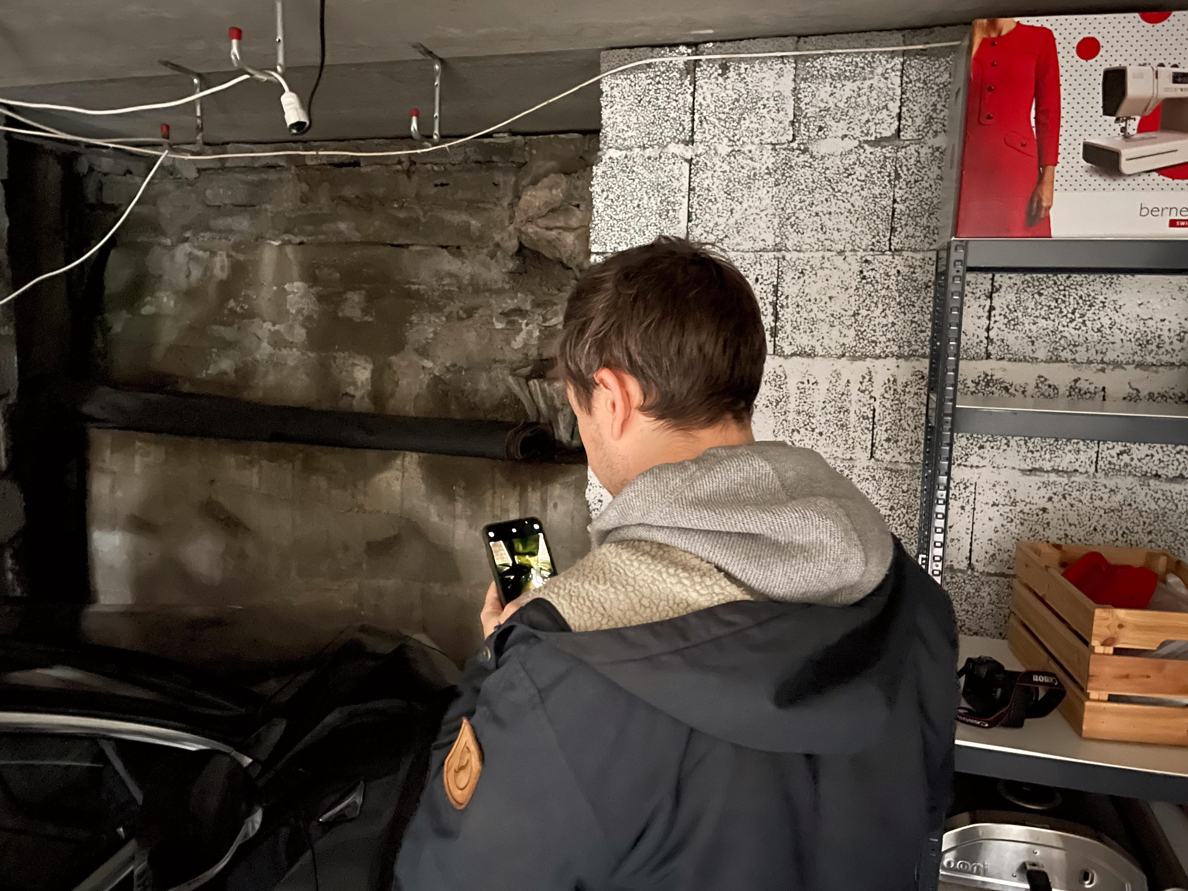 Niklas Plikk tester telefoner i mørk garasje.