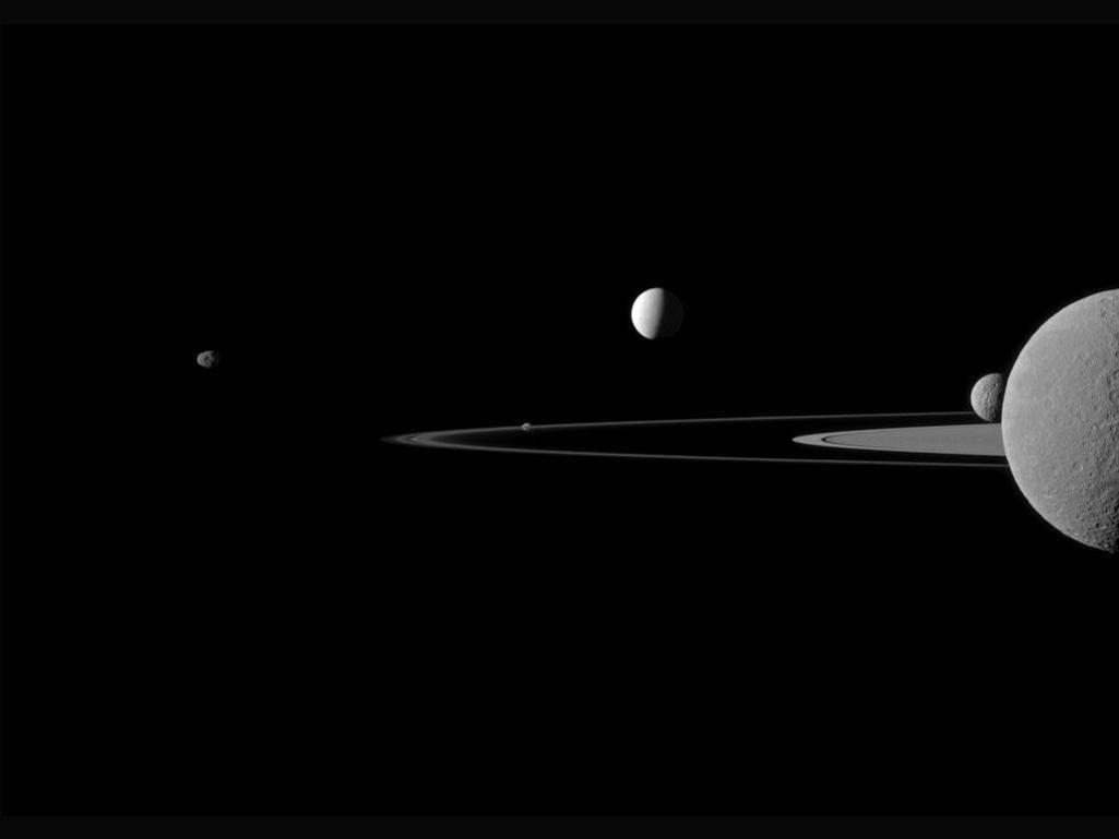 Fem av Saturns måner. Enceladus er nummer tre fra venstre, og den lyseste på bildet. Foto: NASA/JPL-Caltech