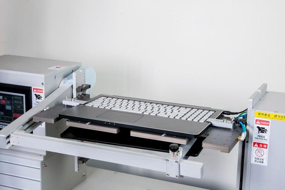 Hengslene på Asus' bærbare datamaskiner testes tusenvis av ganger før de godkjennes. Her er lokket på en av de nyere modellene bøyd hele veien rundt, og mens vi står og ser på fortsetter prosessen.Foto: Asus