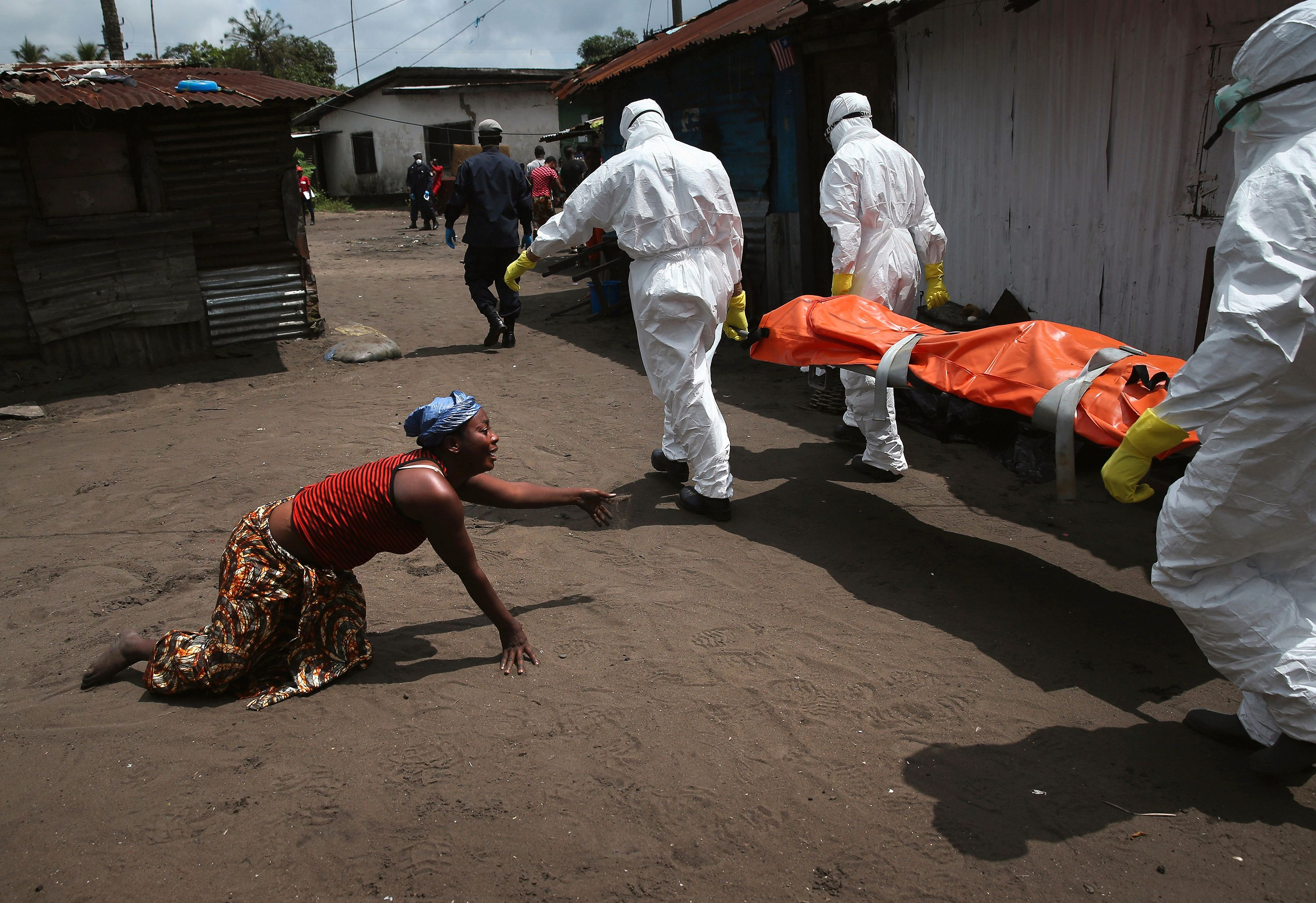 A woman crawls towards the body of her sister as Ebola burial team members take her for cremation on October 10, 2014 in Monrovia, Liberia. The woman had died outside her home earlier in the morning while trying to walk to a treatment center, according to her relatives. The burial of loved ones is important in Liberian culture, making the removal of infected bodies for cremation all the more traumatic for surviving family members. Foto: John Moore / Getty Images, United States, Shortlist, Current Affairs, Professional Competition, 2015 Sony World Photography Awards