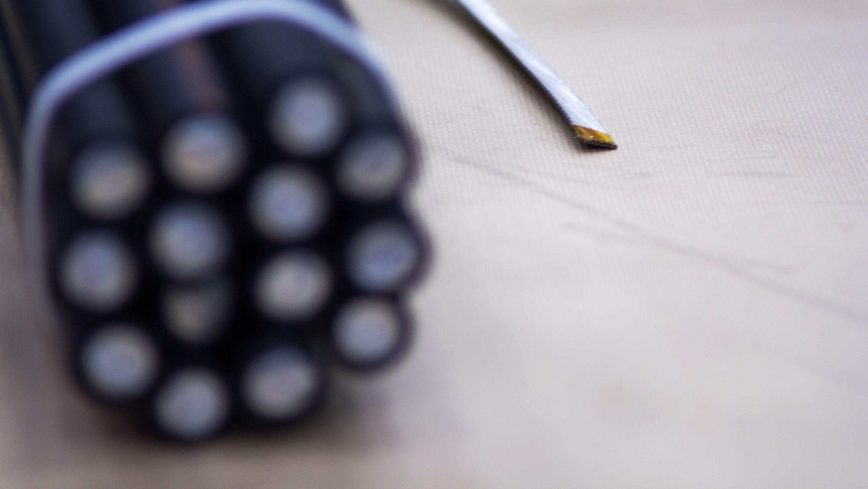 Meget kort fortalt skaper magnetene et magnetfelt ved at en strøm sendes gjennom en spole – og en spole er i bunn og grunn bare en elektrisk leder som er spunnet i sirkel. Skulle CERN laget lederne til magnetene sine ved hjelp av tradisjonelle kabler, måtte de brukt den store klumpen av aluminiumsledere til høyre som takler 25 kV. Det ville gjort magnetene alt for store, og ikke spesielt effektive. Cern tar derfor i bruk en superleder som du ser til høyre – en liten leder som kan lede like mye strøm som den store klasen til venstre. At superledere tas i bruk, er grunnen til at magnetene heter superledende magneter. Foto: Varg Aamo, Hardware.no