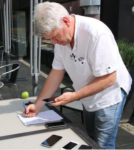 Amobils Espen Swang tester mobiltelefoner i sollys.Foto: Kurt Lekanger, Amobil.no