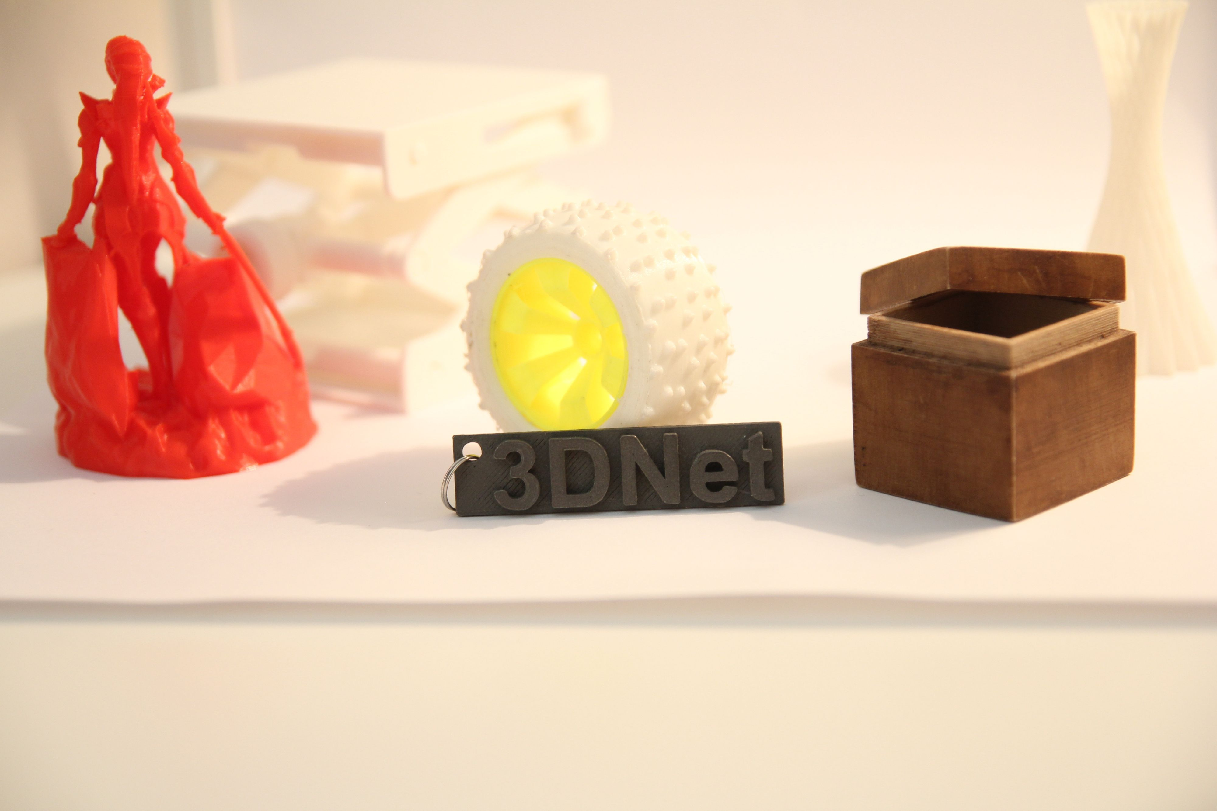 Ulike eksempler på 3D-skrevne objekter. Et hjul til en RC-bil, klart for montering. Det lille skiltet med 3Dnet-logoen er laget med et filament som består av 30 prosent rustfritt stål. Den lille boksen kjennes ut som om den er av tre, og filamentet består da også av 30 prosent trevirke.