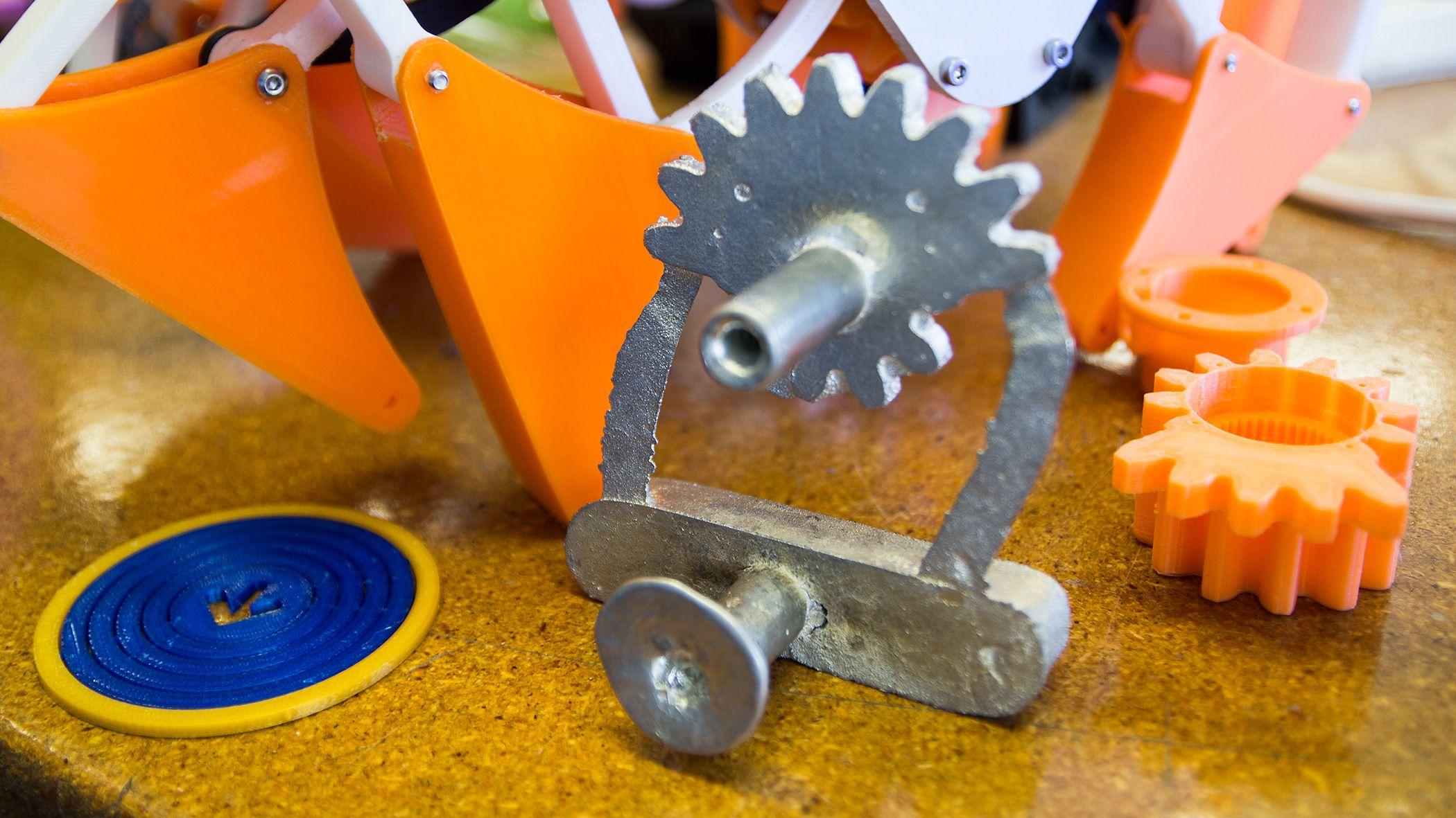 Muligheten til å lage billige støpeformer er én av mange ting 3D-skrivere egner seg godt til. Dette tannhjulet i tinn var et av Type A Machines første forsøk på nettopp dette. I bakgrunnen står en liten Strandbeest-basert robot, skrevet ut og klar til å spasere.Foto: Varg Aamo, Hardware.no