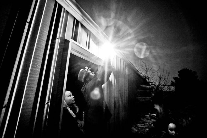 John Mast fyrer opp i gasslampen, mens døtrene venter på å få smake lønnesirupen som lages ute, over åpen ild. Foto: Stein J. Bjørge