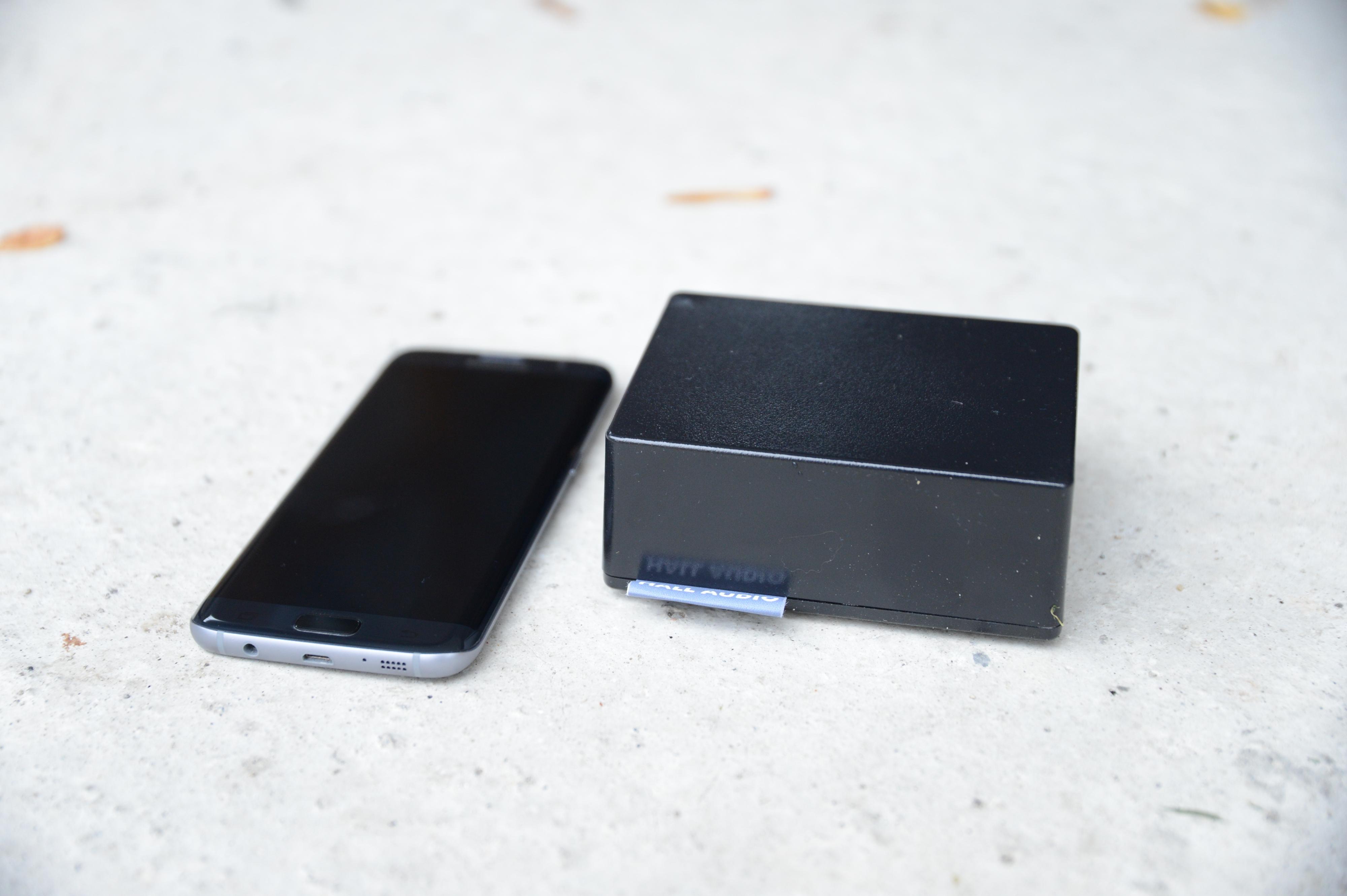 Selve forsterkeren er ikke så stor av seg. Her ved siden av en Samsung Galaxy S7 Edge.