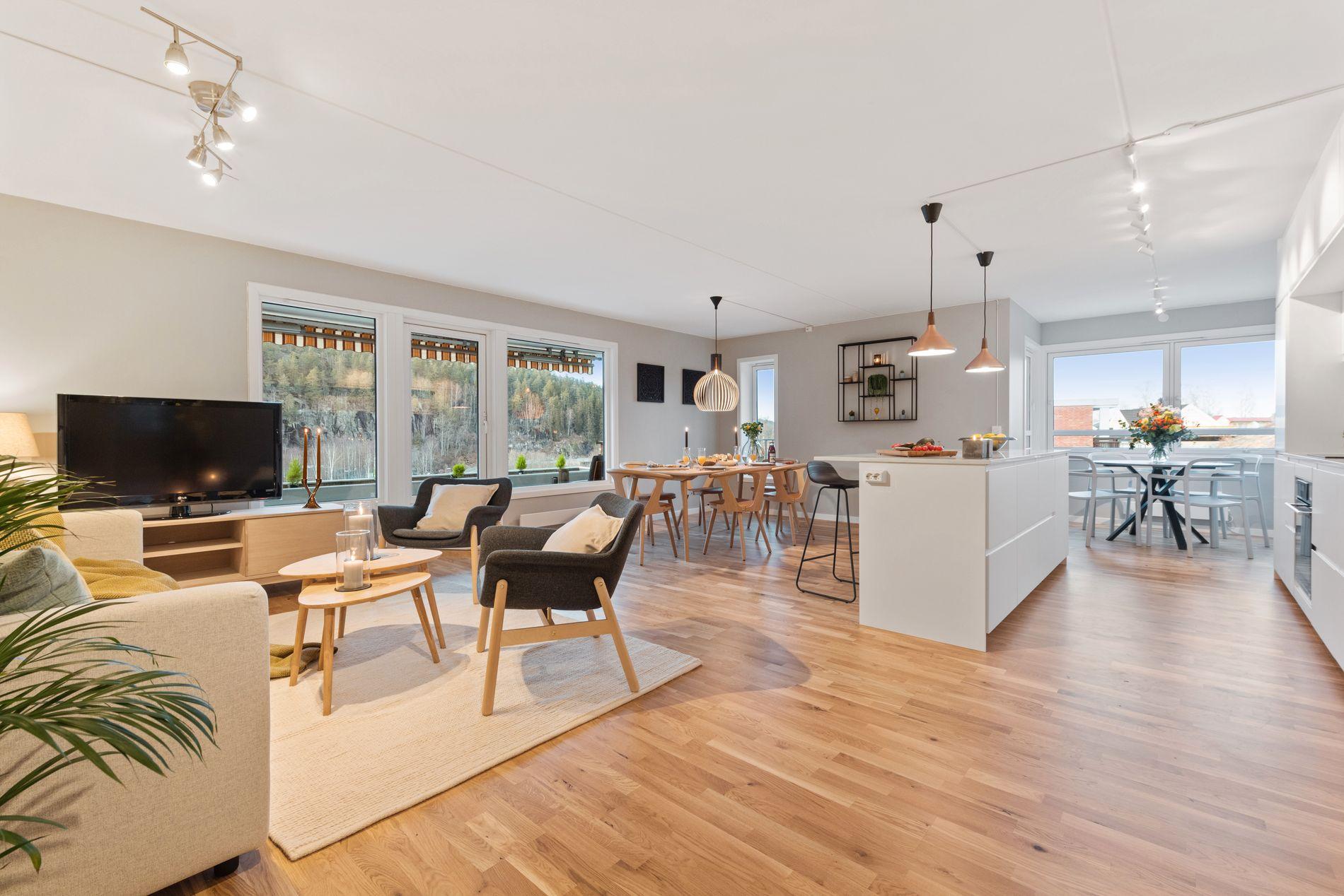 NYTT OG STORT: Før leiligheten ble lagt ut for salg, fjernet eieren veggen mellom kjøkken og stue, og monterte nytt kjøkken og ny kjøkkenøy.