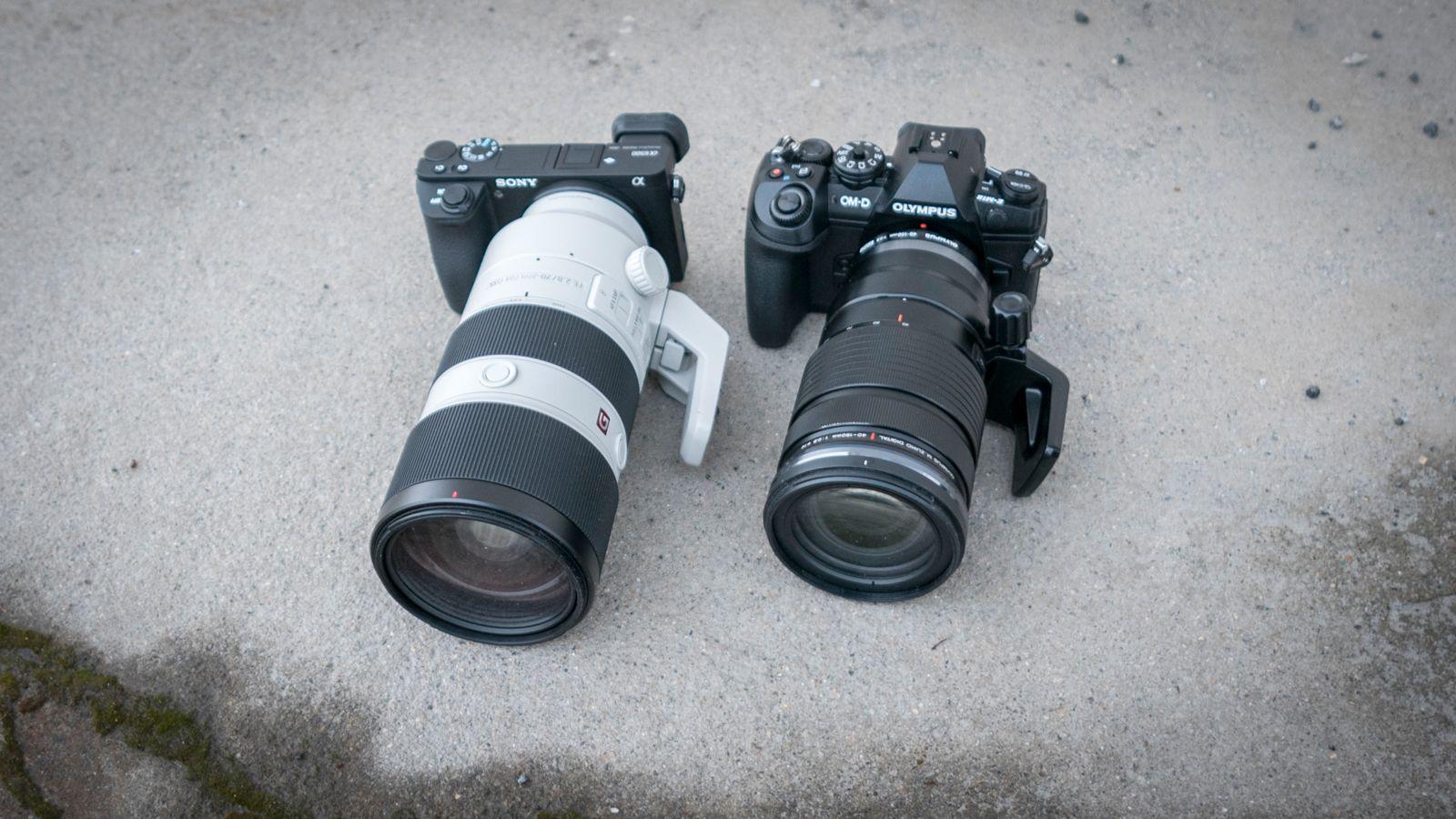 a6500 (t.v.) er et veldig kompakt systemkamera, men omtrent all av Sonys gode optikk og lyssterke optikk er designet for fullformat, og da forsvinner «kompakthetsargumentet» raskt ut av vinduet. Her plassert ved siden av Olympus OM-D E-M1 II med objektiver med samme blenderåpning og effektive brennvidde.
