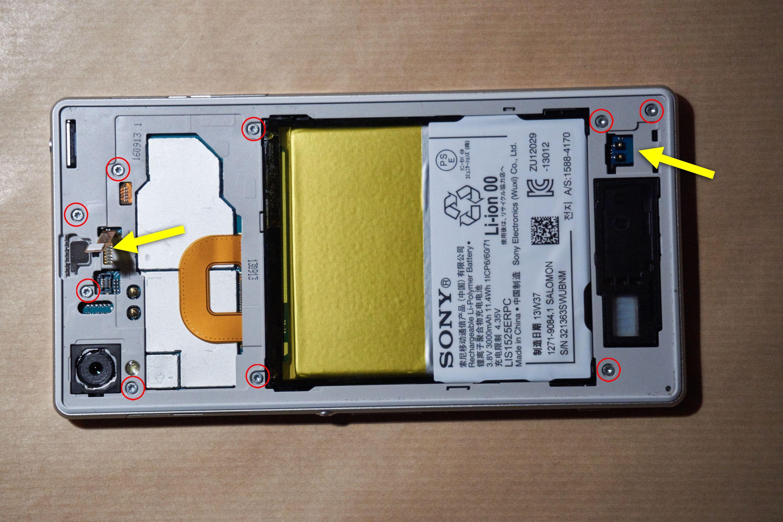 Slik så altså telefonen ut nå. Før vi kunne fortsette, måtte vi skru ut alle skruene markert med rødt. De to gule pilene markerer de to bitene vi nettopp tok ut.