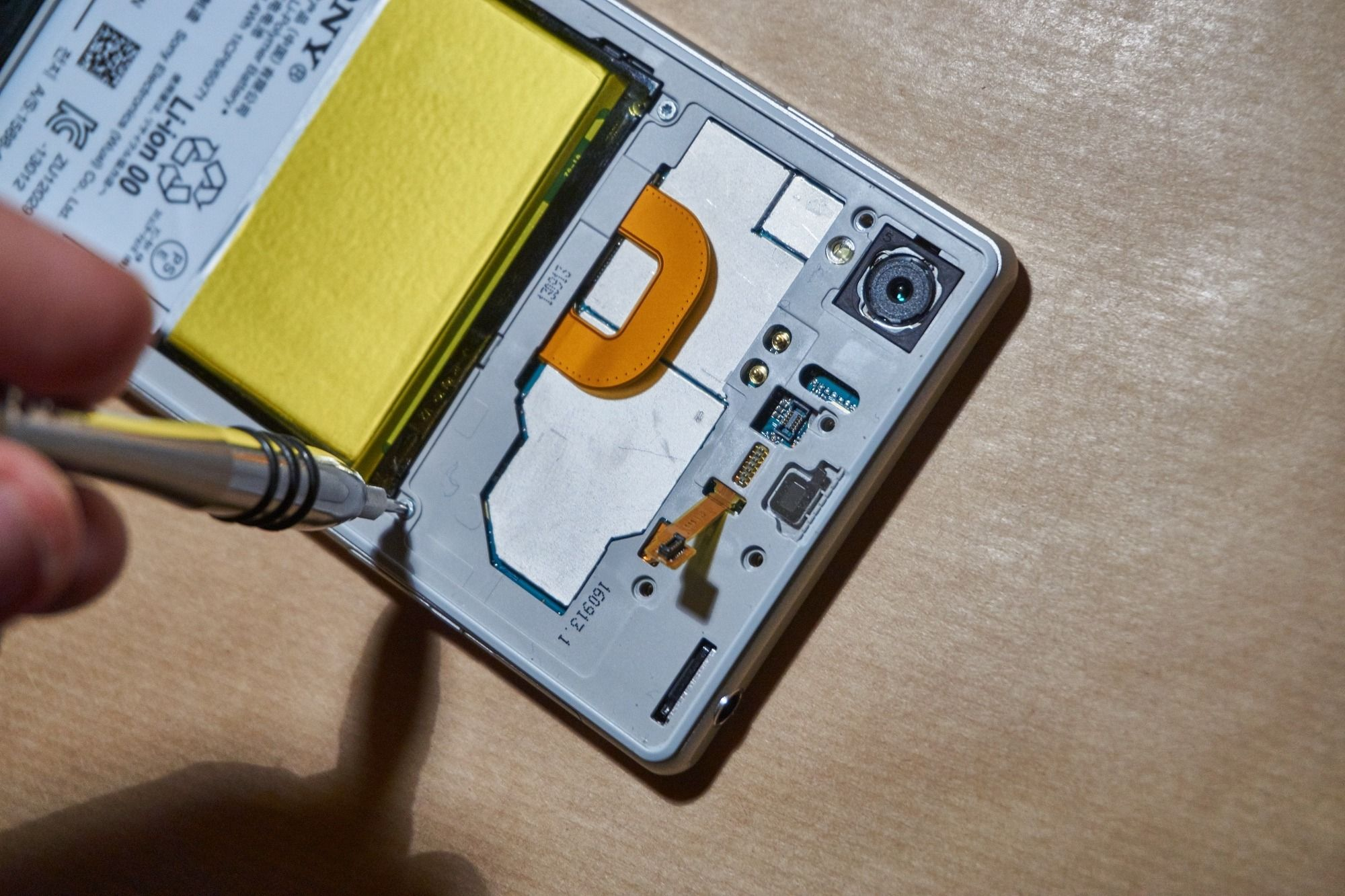 Batteriet kobles på, og rammen skrus inn.