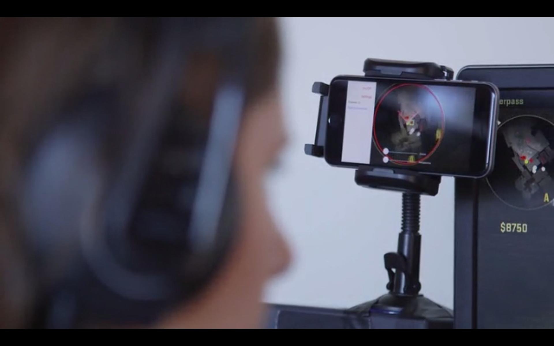Halsbåndet bruker kameraet på mobilen til å fange opp informasjon på spillskjermen.