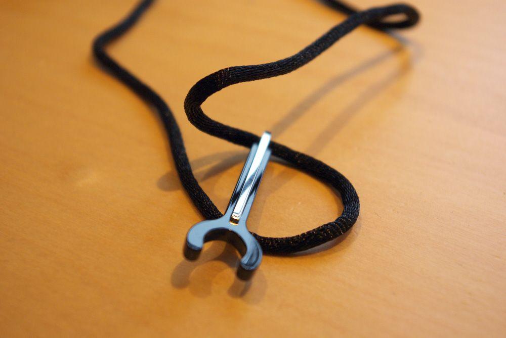 Salgspakken inneholder også en snor som kan brukes til å feste håndfrien rundt nakken.