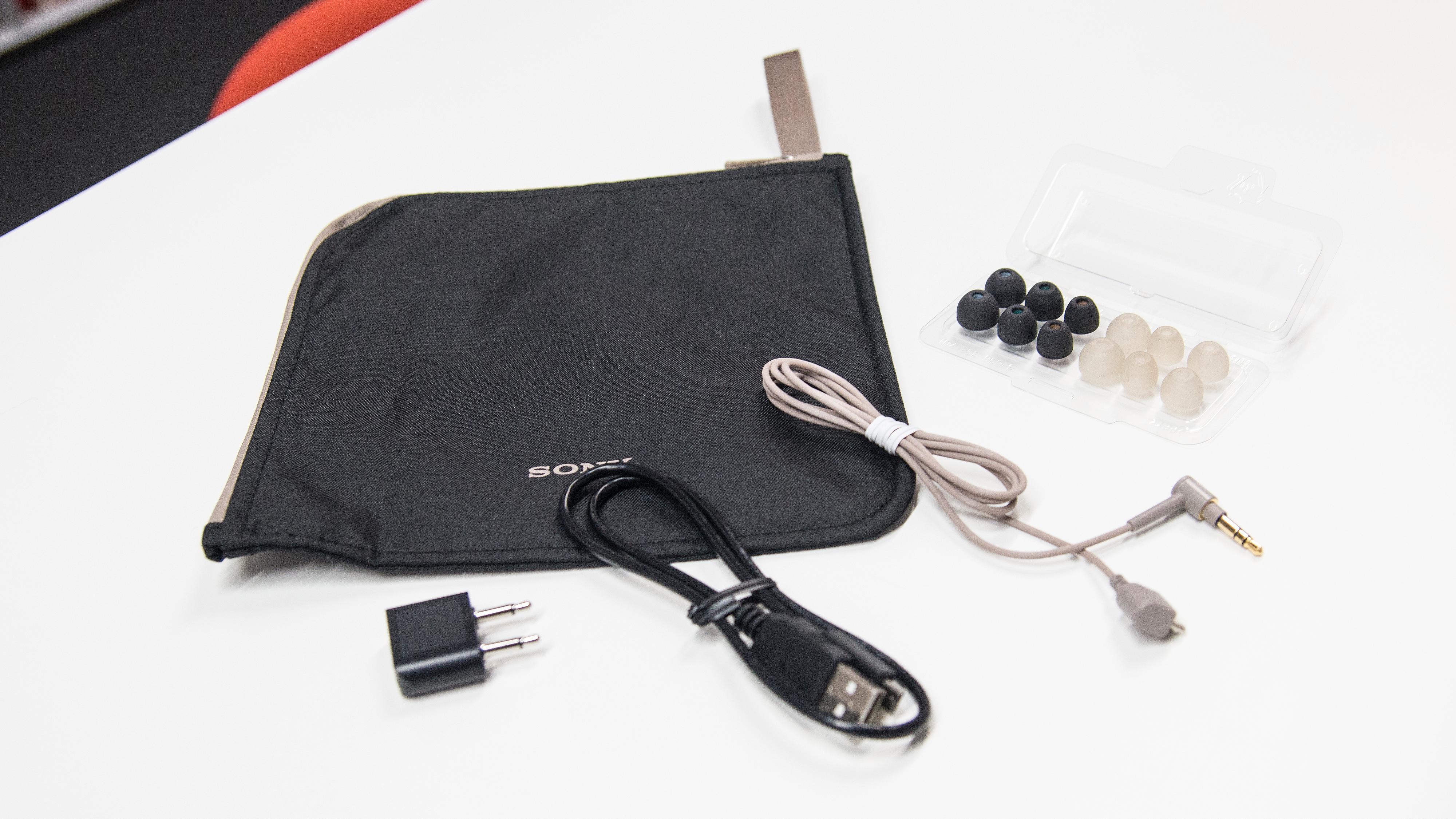 Innholdet i eska: Bæreveske i tøy, ladekabel, flyadapter, microUSB-til-minijack-kabel og sett med puter i silikon og skum.