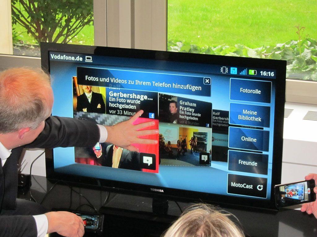 Her er telefonen koblet til en TV ved hjelp av en dokk. Kobler du strøm til Doken, så kan du bruke løsningen som Android-PC. En egen fjernkontroll følger med, eller du kan koble USB-mus og tastatur til dokken. Men du kan ikke betjene skjermen med fingrene slik det ser ut som denne karen forsøker.