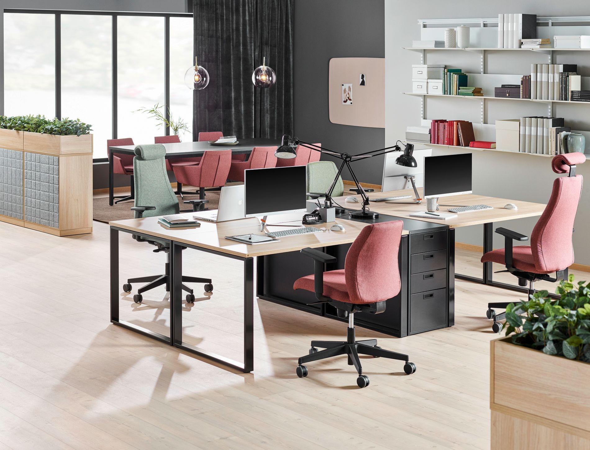 Bildet viser en klassisk open office-løsning. Her åpner man opp mellom skrivebordene og møterommet blant annet ved hjelp av kommoder og planter som skillevegg.