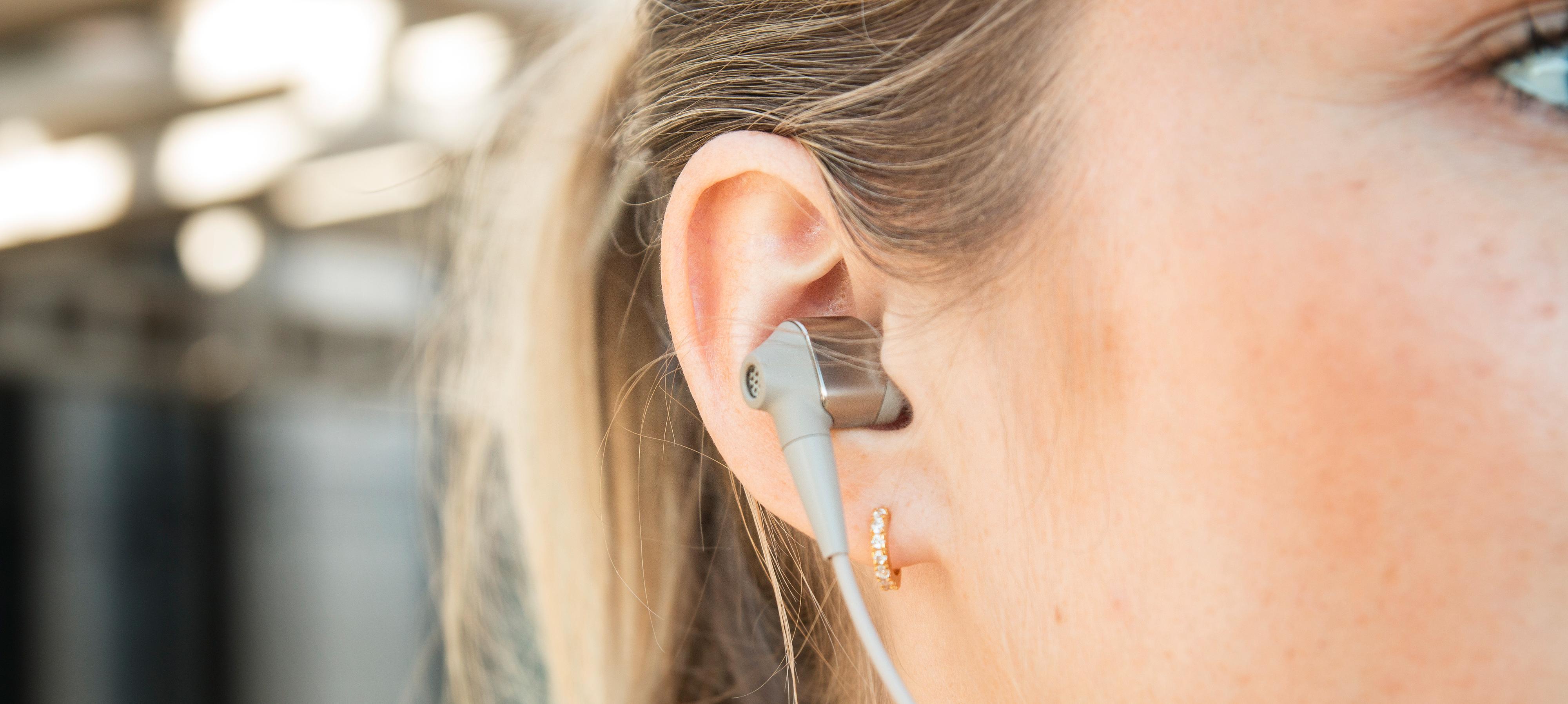 WI-1000X stikker middels langt ut av øret, men nakkekragen gjør at de sitter godt på plass.