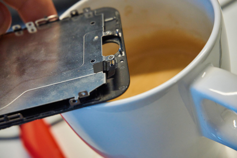 17. Vi hadde ingen varmepistol for hånden, men ved å holde skjermen inntil en varm kopp kaffe fikk vi løsnet limet på kabelen til hjemknappen. Vi gjorde IKKE som på bildet – det er kun en illustrasjon, og er både ineffektivt og utsetter delene for fuktighet!