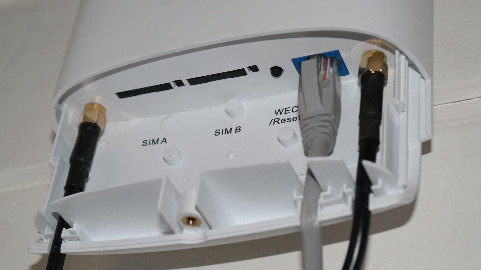 Under et deksel finner du porter for to simkort, og to punkter for tilkobling av ekstern antenne (de sorte kablene). Den grå kabelen går til strømforsyningen. Foto: Espen Irwing Swang, Tek.no