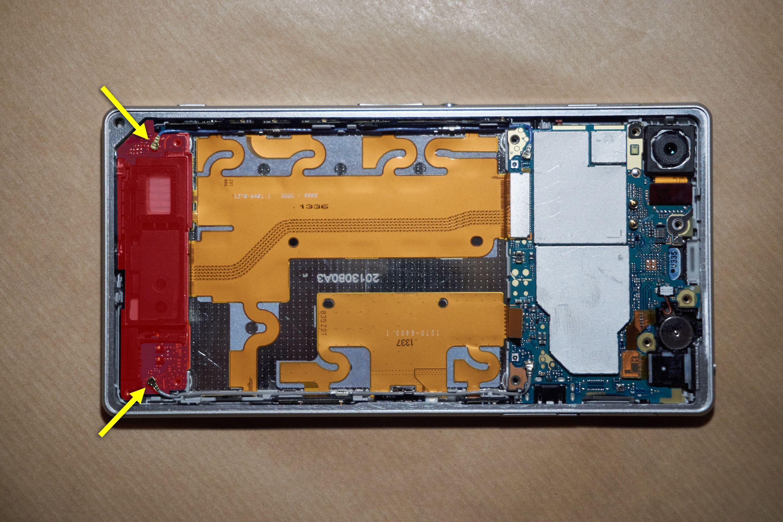 Den svarte biten nederst (markert i rødt) måtte ut for å komme til skjermtilkoblingen. De to kontaktene (gule piler) trengte vi imidlertid ikke fjerne.