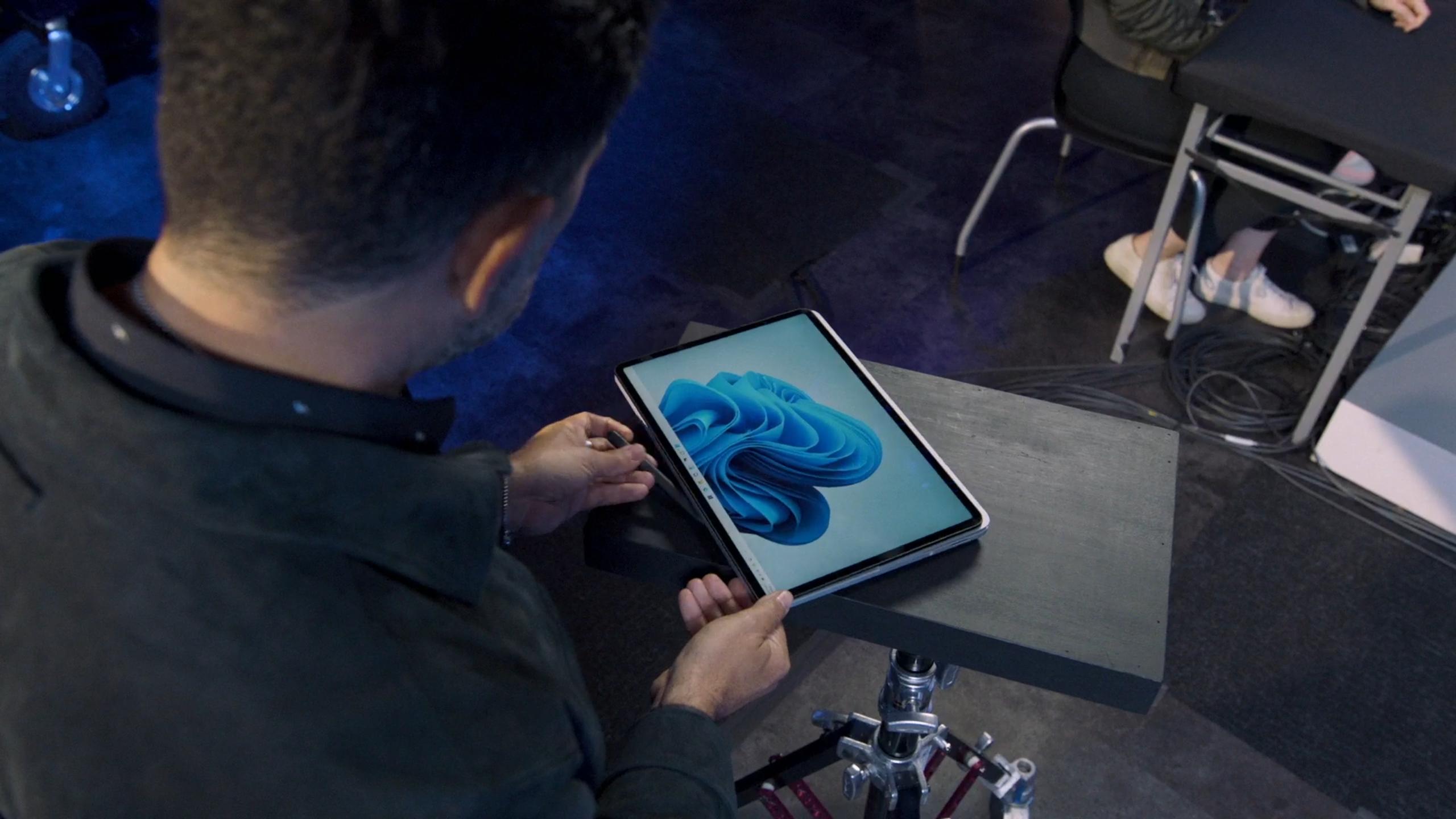 Surface Laptop Studio i «Studio-modus». Her ser vi også Panos Panay hente frem Surface Slim Pen 2, som har ligget magnetisk festet til undersiden av maskinen.