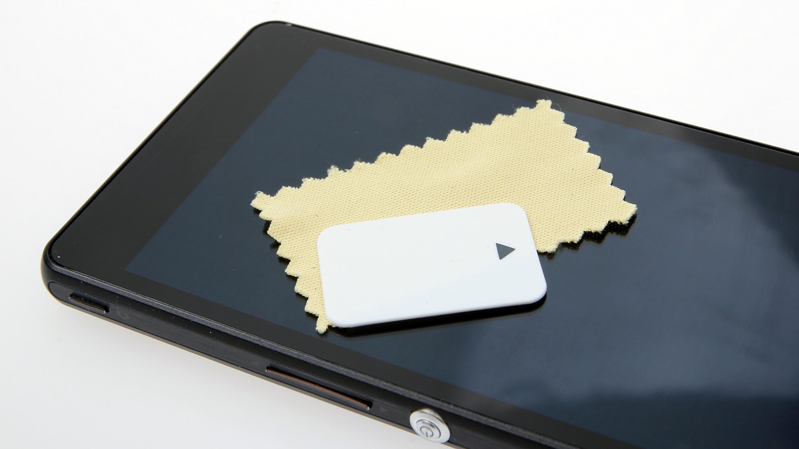 Er dette verdens minste pusseklut? Den følger med, sammen med en liten dings for å fjerne plastfilmen foran skjermen.Foto: Kurt Lekanger, Amobil.no