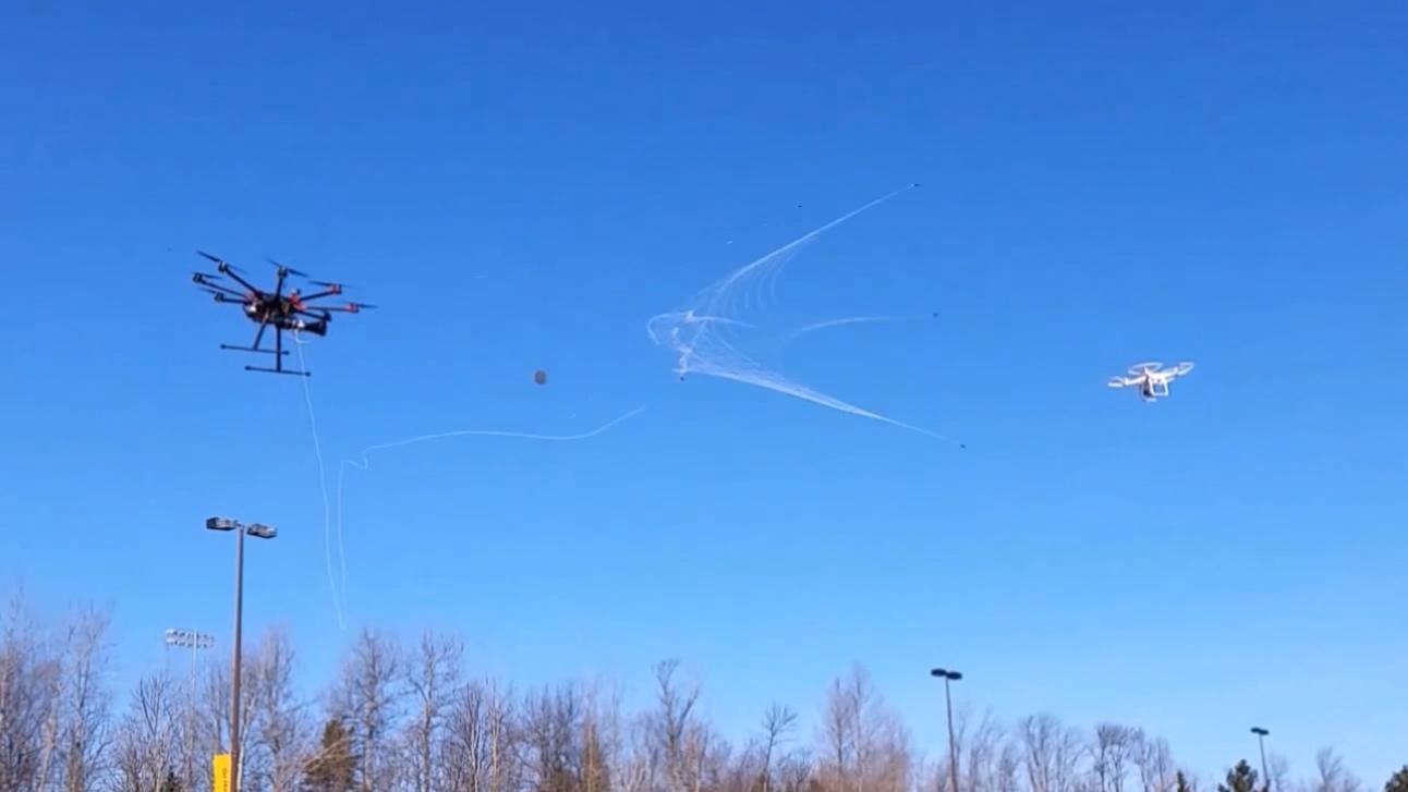 Her fanger dronen en annen drone med et nett